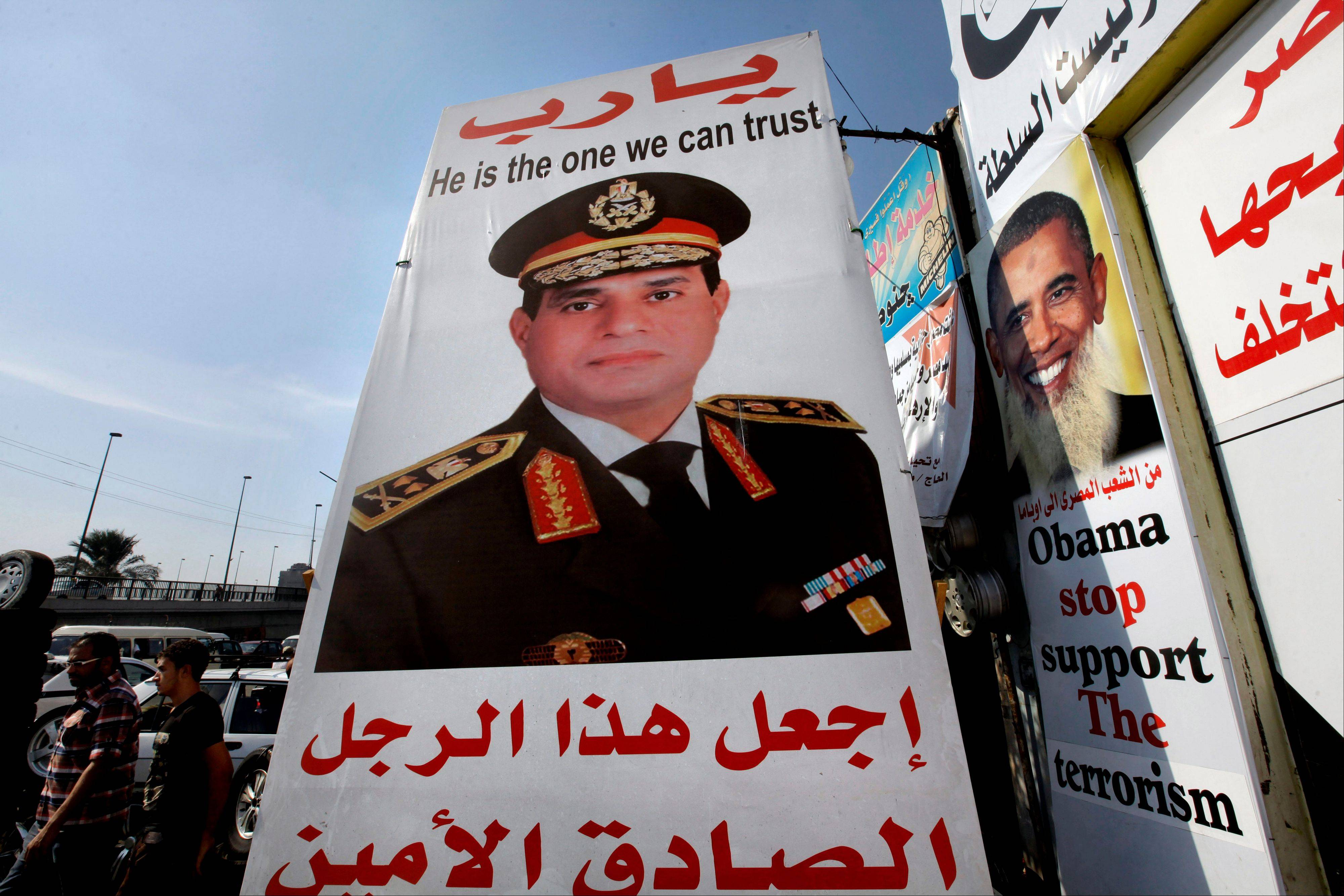 "Egyptians walk behind a banner supporting Egyptian Army Chief Lt. Gen. Abdel-Fattah el-Sissi, center, with Arabic that reads, ""God, keep this truthful honest man,"" in Cairo, Egypt, Monday, Aug. 5, 2013. More than a month after Morsi's ouster, thousands of the Islamist leader's supporters remain camped out in two key squares in Cairo"