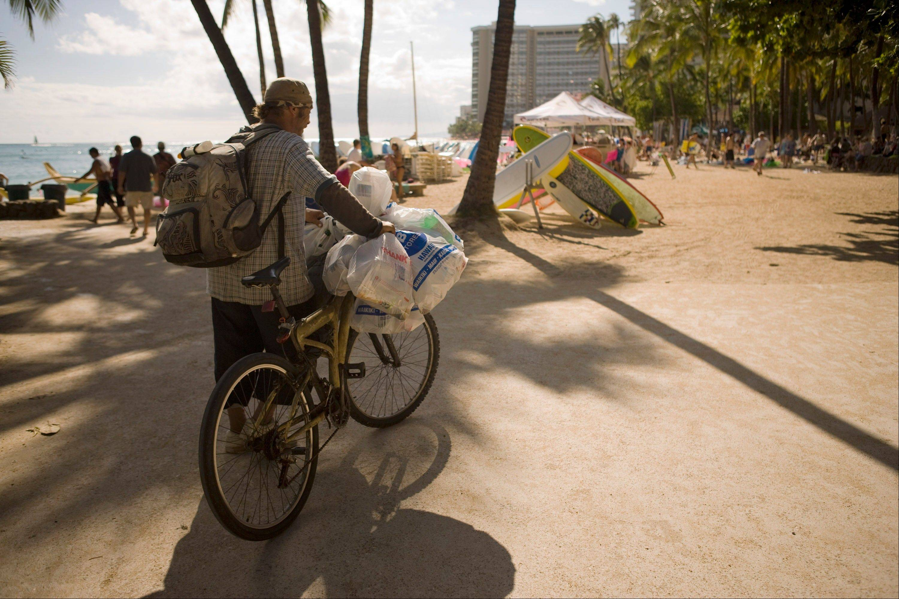This July 12, 2010 file photo shows a homeless man who goes by the name Guy West collecting cans on Waikiki Beach, Monday, in Honolulu. Homelessness increased 15 percent on Oahu since last year according to a recent report. A growing number of homeless are not from Hawaii but make the most of their situation by taking advantage of inviting beaches and support services. State lawmakers are struggling with the visible problem of homelessness in tourist areas and some have proposed a contentious idea to use state money to fly the homeless back to wherever they came from.