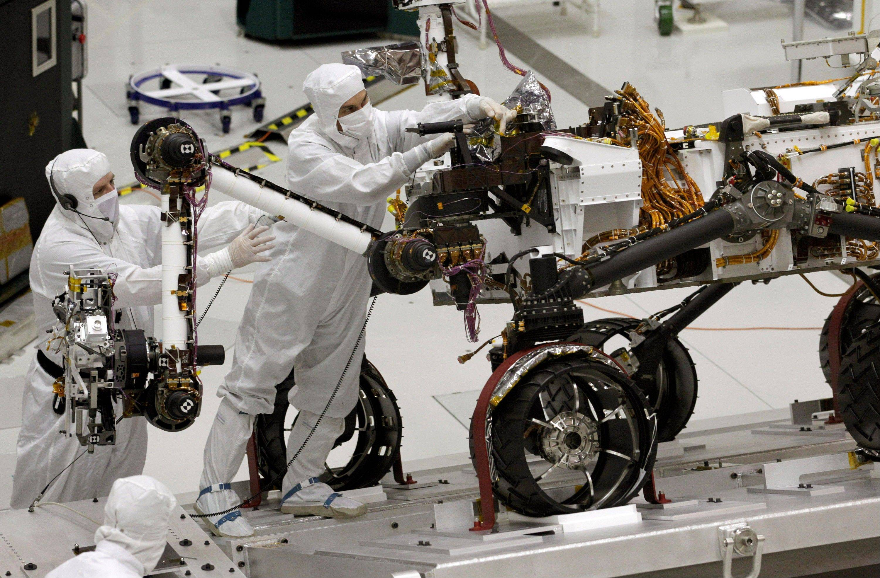 This Sept. 16, 2010 file photo shows engineers working on the Mars rover Curiosity at NASA's Jet Propulsion Laboratory in Pasadena, Calif. Curiosity celebrated its first year on Mars and is driving toward a mountain in a journey that will take months.