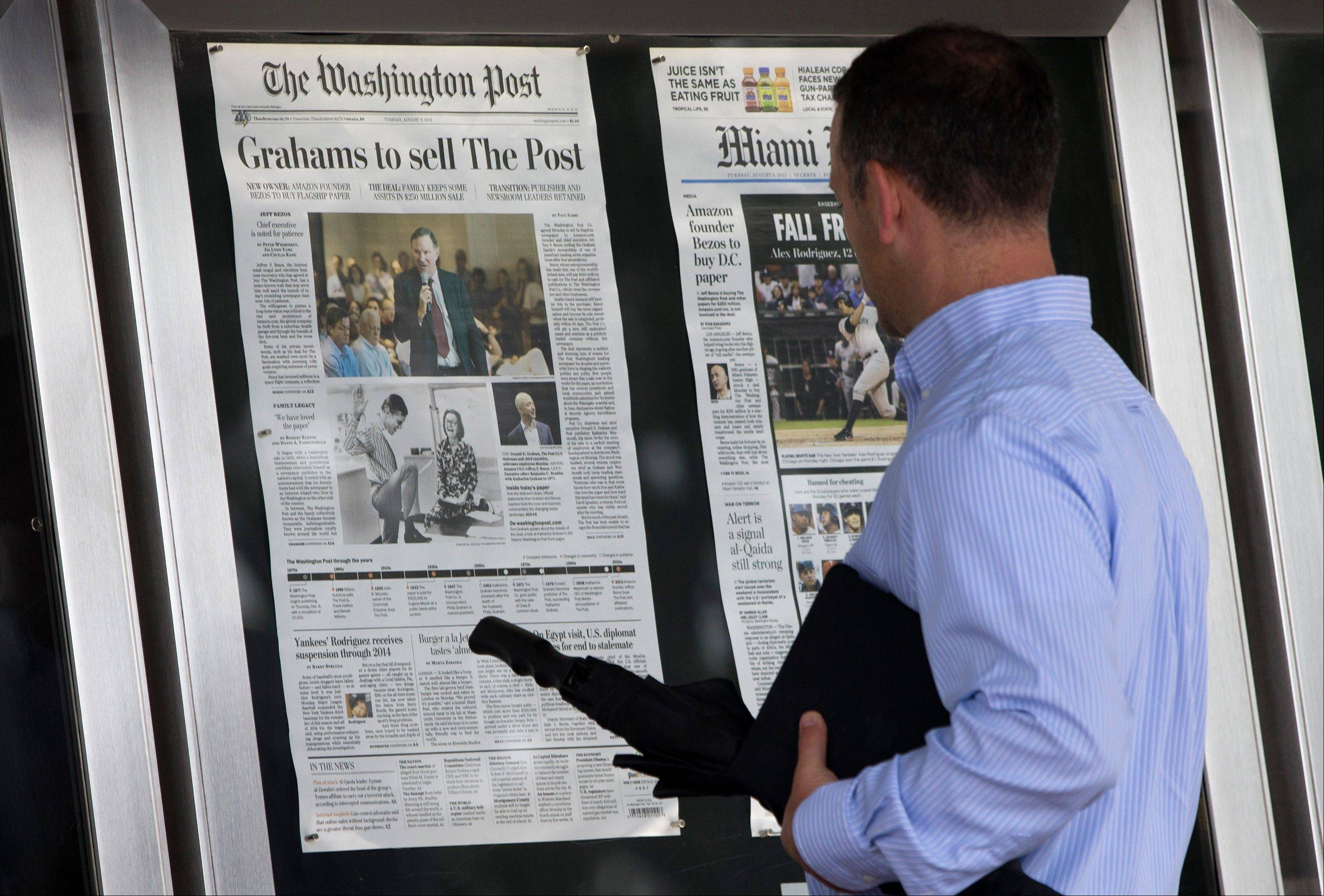 A visitor views the front page of the Washington Post, displayed outside the Newseum in Washington, on Tuesday, a day after it was announced that Amazon.com founder Jeff Bezos bought the newspaper for $250 million.