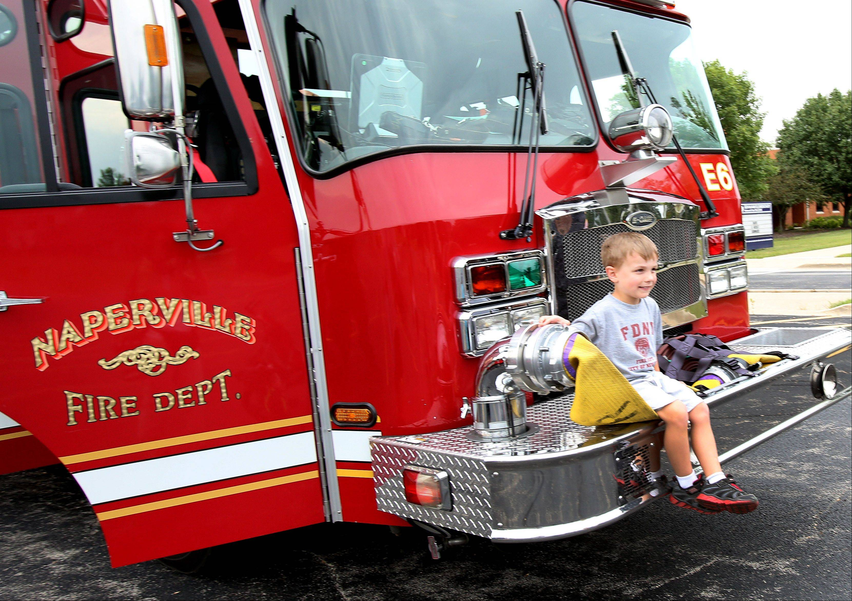 Sean Traynor,5, sits on a fire truck during National Night Out in Naperville in the High Meadow subdivision.