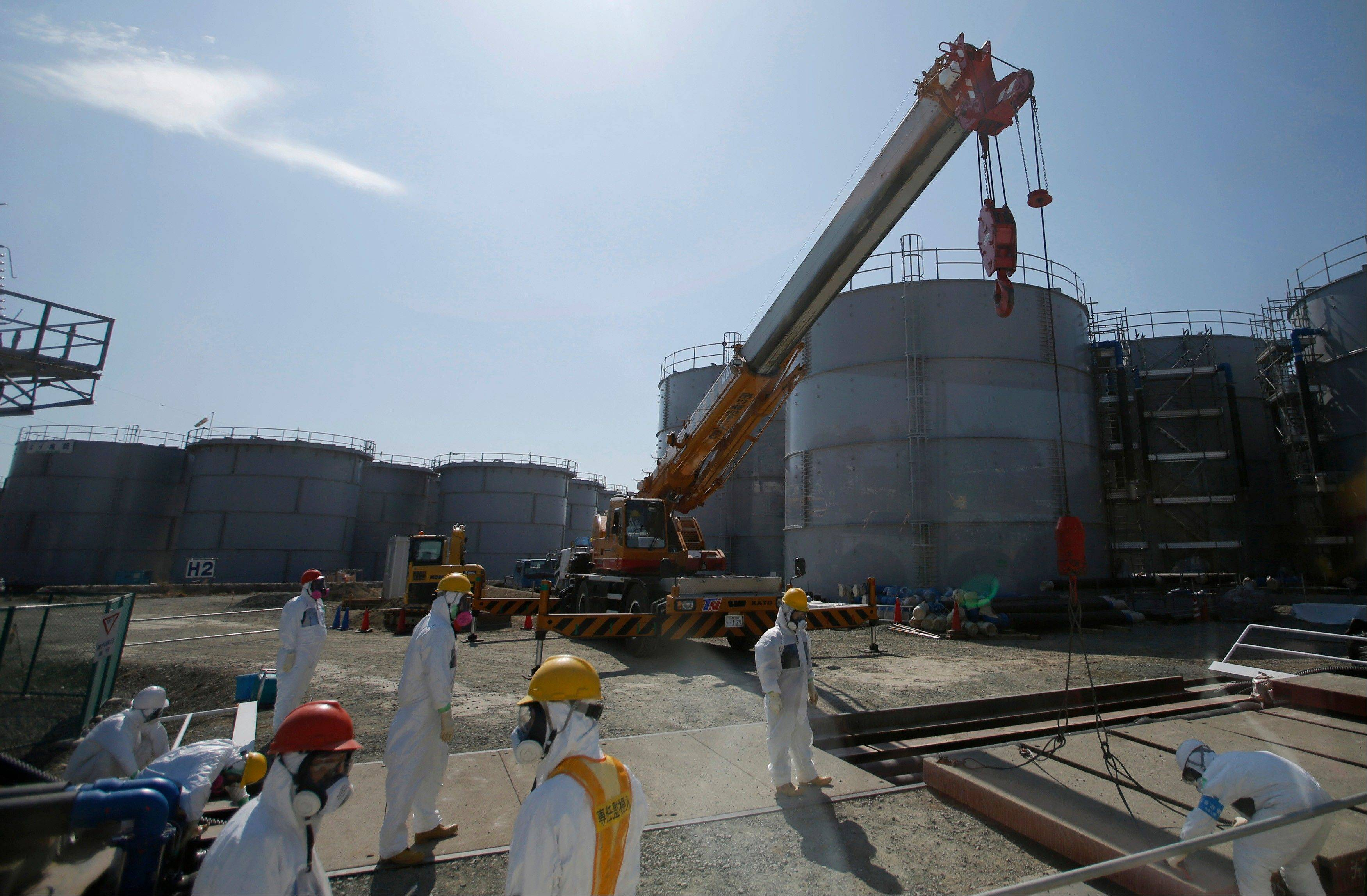 Workers wearing protective gear take a survey near tanks of radiation contaminated water at Tokyo Electric Power Co.�s Fukushima Dai-ichi nuclear power plant in Okuma town, northeast of Tokyo. The operator of the wrecked Fukushima nuclear power plant says it is struggling with its latest efforts to stop contaminated underground water leaks from running into the sea.