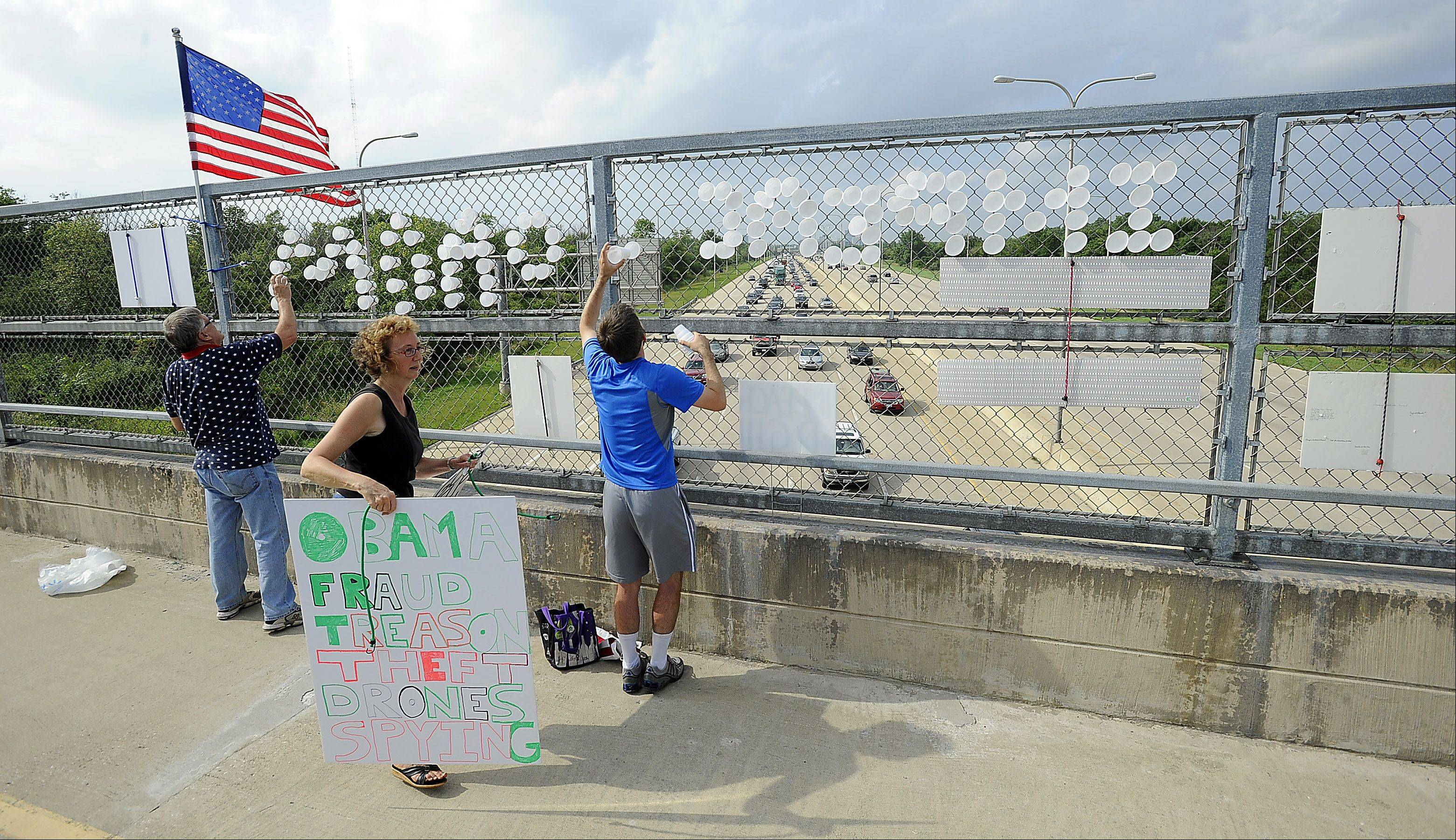 Nancy Jacques of Palatine and Gerry Plath, left, of Schaumburg hang protest materials on the bike bridge over I-290/Route 53 calling for the impeachment of President Barack Obama on Tuesday near Busse Woods.