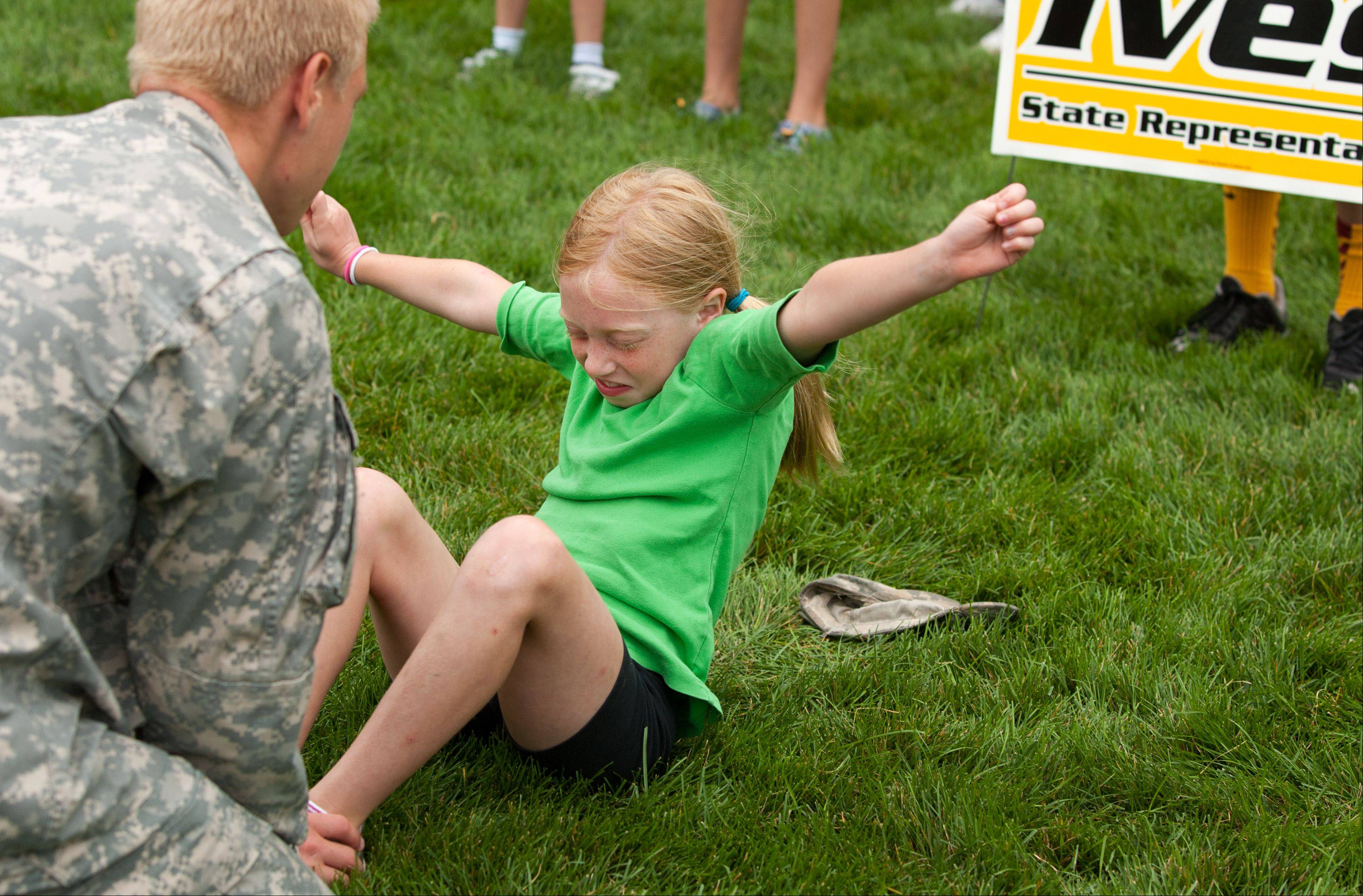 Louisa Ives, 9, of Wheaton, perfects her timed sit-ups with her brother, Nick, a cadet at West Point, during the inaugural health and fitness boot camp for children ages 3 through 12 at Cantigny Park in Wheaton. State Rep. Jeanne Ives of Wheaton sponsored the free camp.
