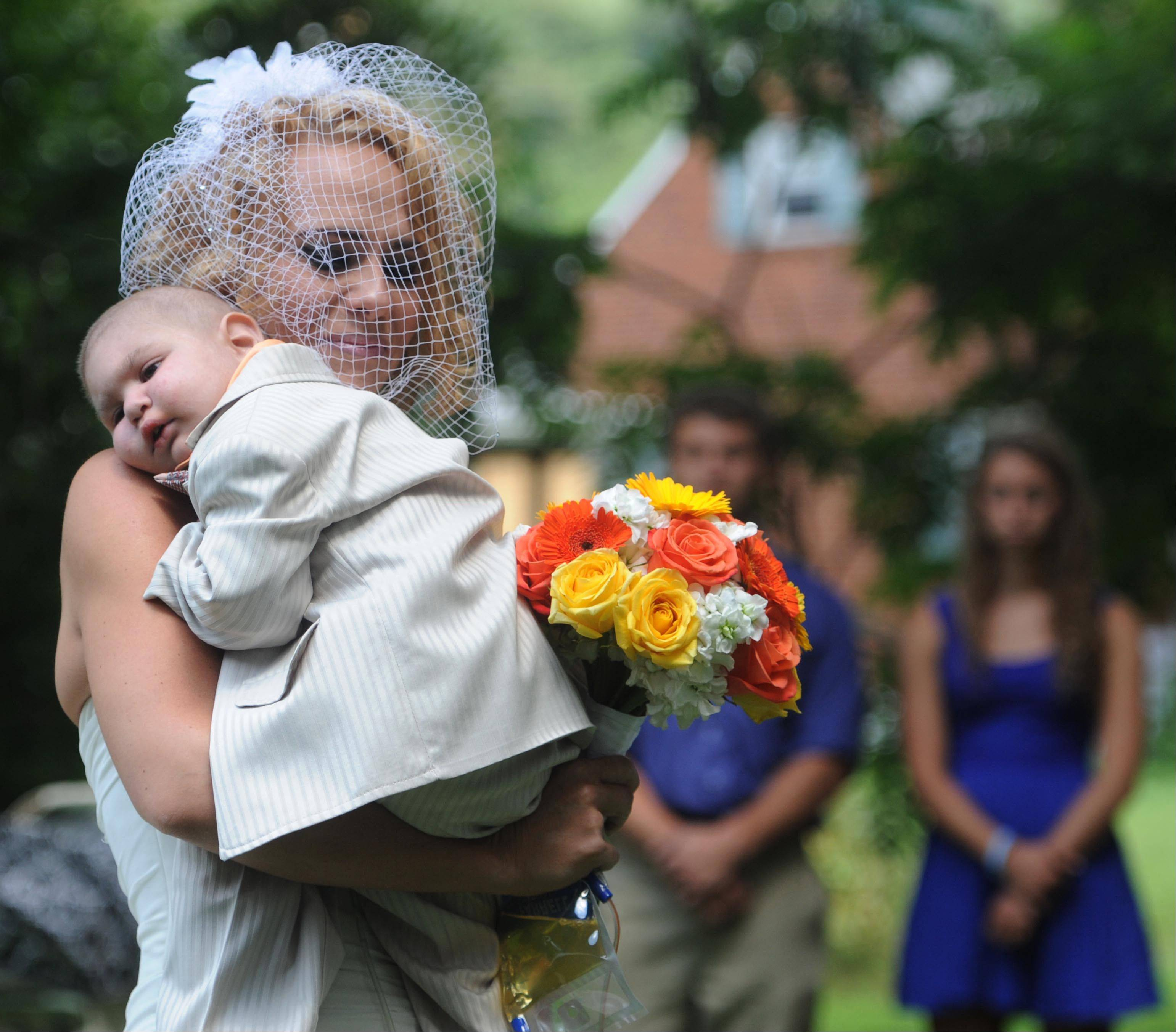 This Aug. 3, 2013 file photo, Christine Swidorsky carries her son and the couple�s best man, Logan Stevenson, 2, down the aisle to her husband-to-be Sean Stevenson during the wedding ceremony in Jeannette, Pa., Christine Swidorsky Stevenson says on her Facebook page that Logan died in her arms at 8:18 p.m. Monday, Aug. 5, 2013, at their home in Jeannette, about 25 miles east of Pittsburgh. Logan, who was born Oct. 22, 2010, was diagnosed shortly after his first birthday with acute myeloid leukemia. The Stevensons abandoned an original wedding date of July 2014 after learning from doctors late last month that their son had two to three weeks to live.