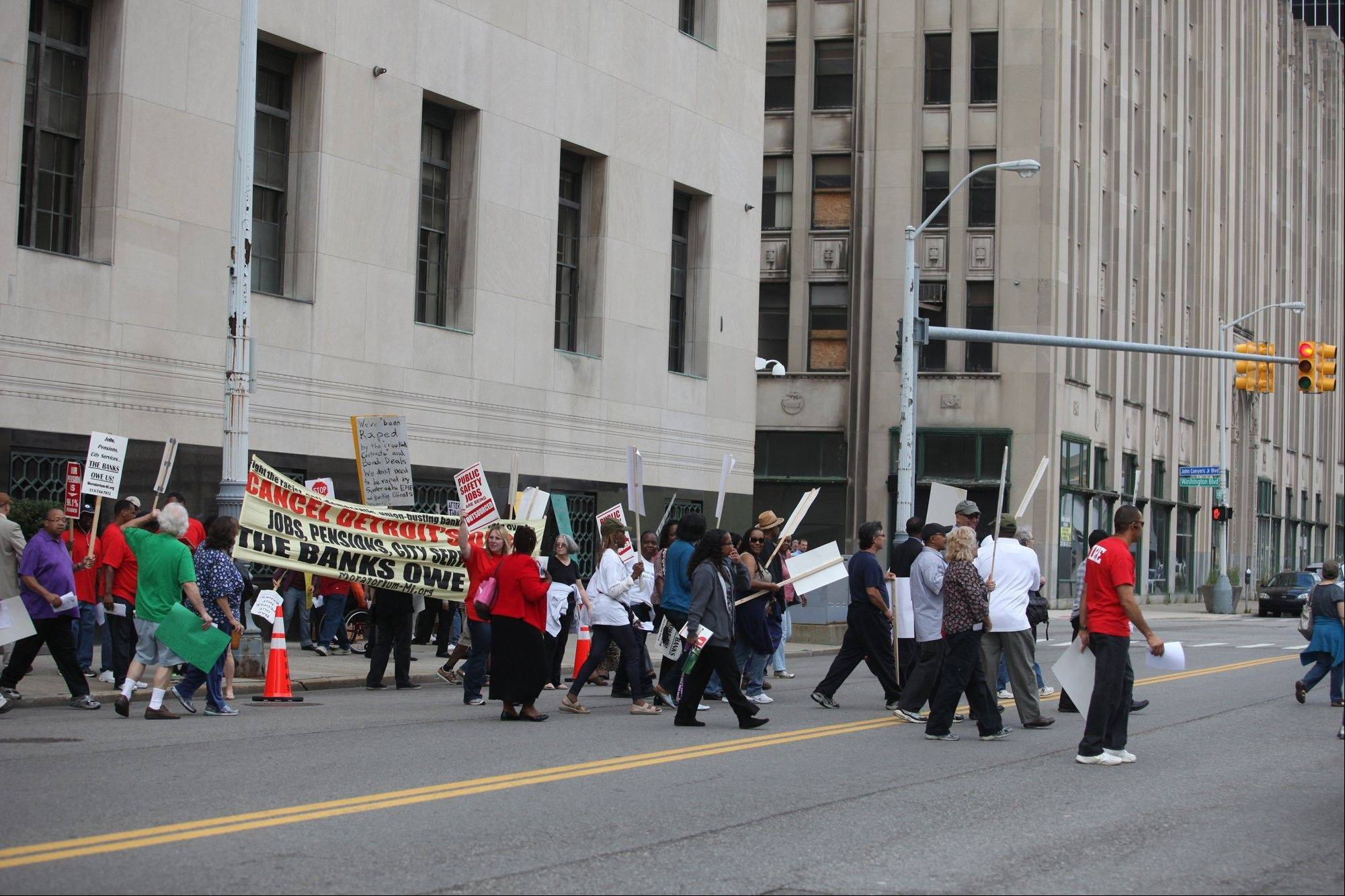 Protesters cross the street in front of federal court in Detroit Friday, Aug. 2, 2013. Candidates in Detroit�s mayoral primary are racing to lead the largest U.S. city ever to file for bankruptcy, while yielding complete control of its finances to a state-appointed emergency manager.