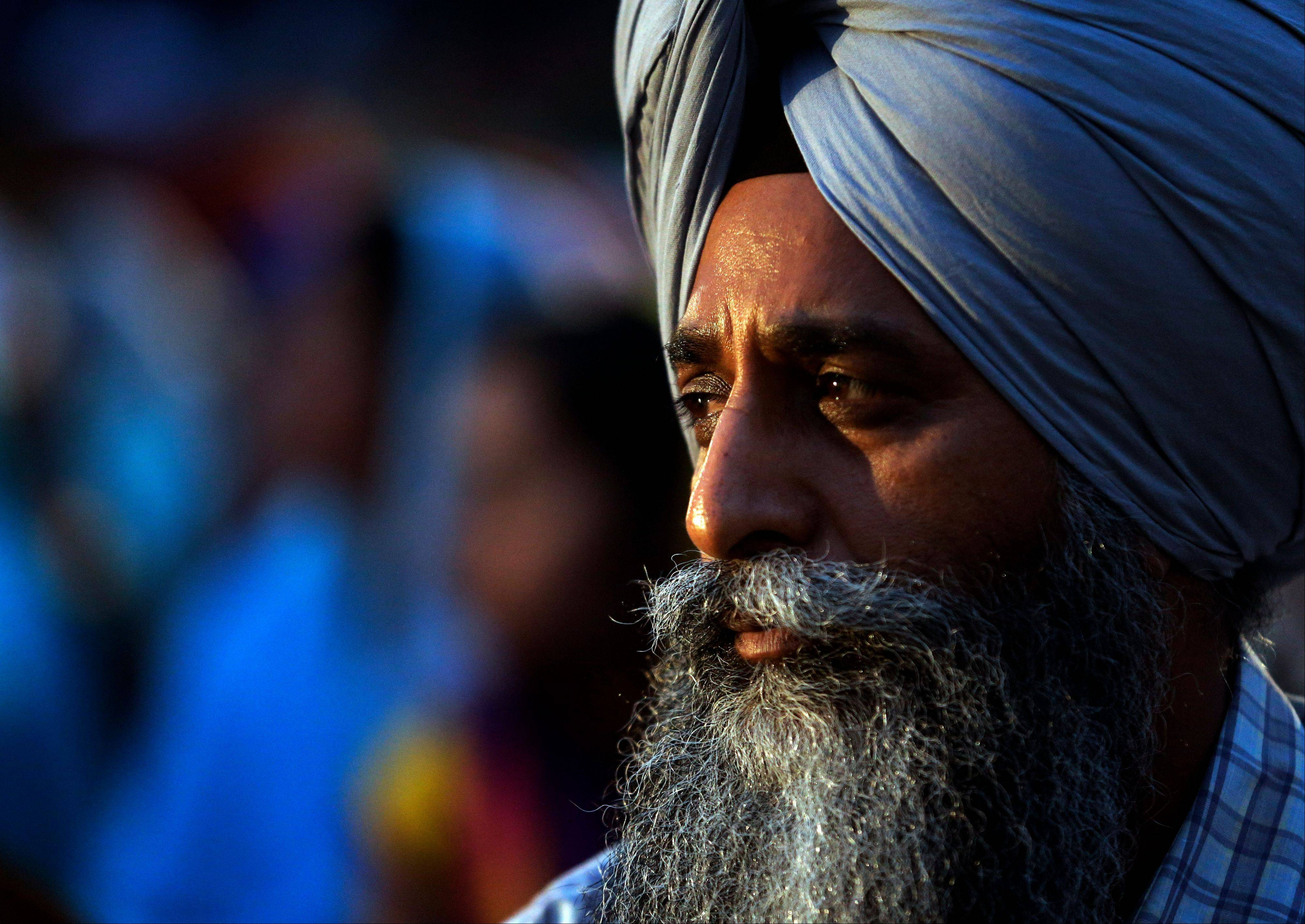 Getinder Singh Kigtra participates in a candlelight vigil at the Sikh Temple of Wisconsin to mark the one-year anniversary of the shooting rampage that left six dead, Monday, Aug. 5, 2013, in Oak Creek, Wis. The white supremacist gunman, who wounded five other worshippers and an Oak Creek police officer, killed himself in the parking lot.