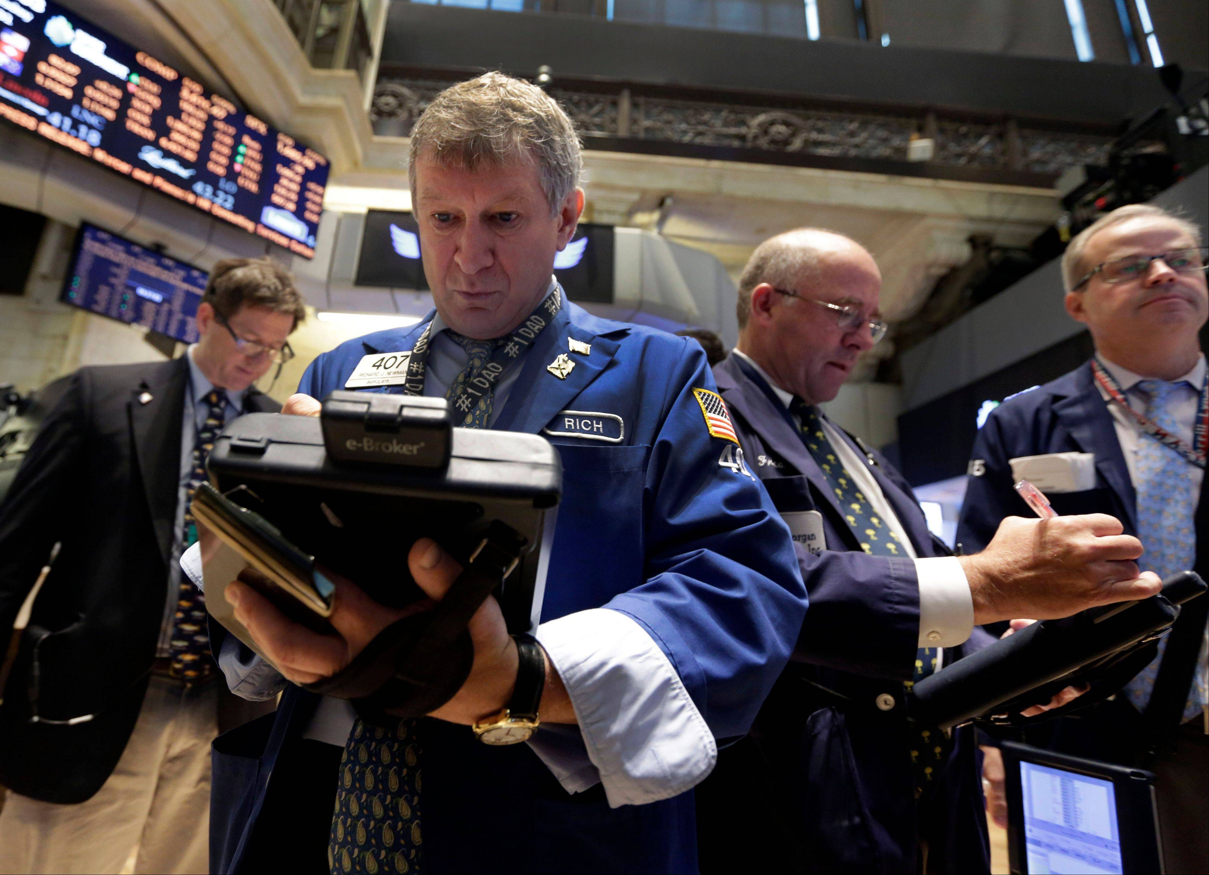 Associated Press/July 31, 2013Richard Newman, second left, works with fellow traders on the floor of the New York Stock Exchange.