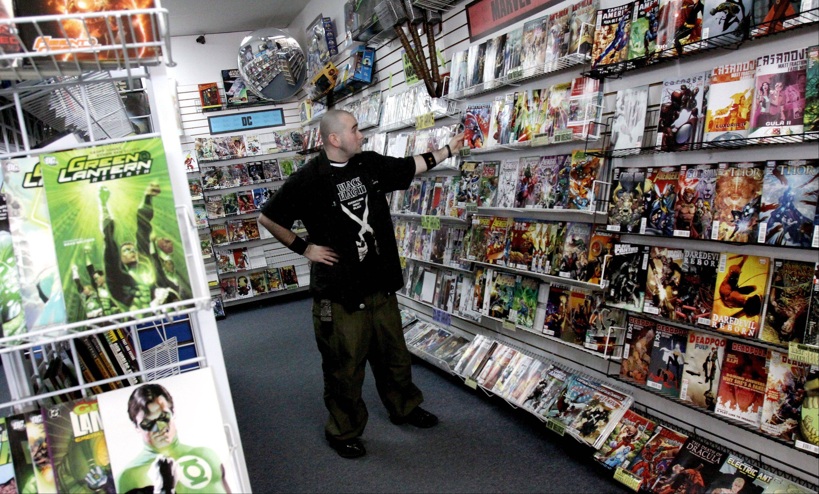 An employee shelves books at the Graham Cracker Comics store in Naperville. The local comic-store chain, with several locations in the suburbs, will again sell old and new comics at the Chicago Comic Con in Rosemont.