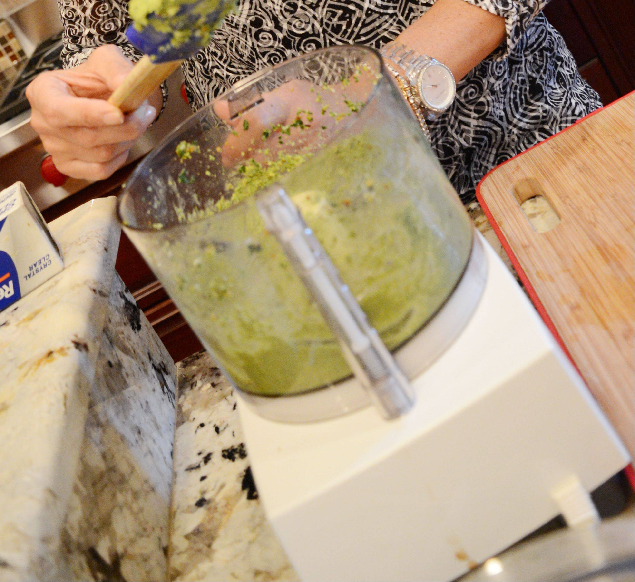 Nancy Bertschy prepares pistachio basil spinach butter to top baked salmon. She makes a large batch of the butter and keeps it in the freezer.