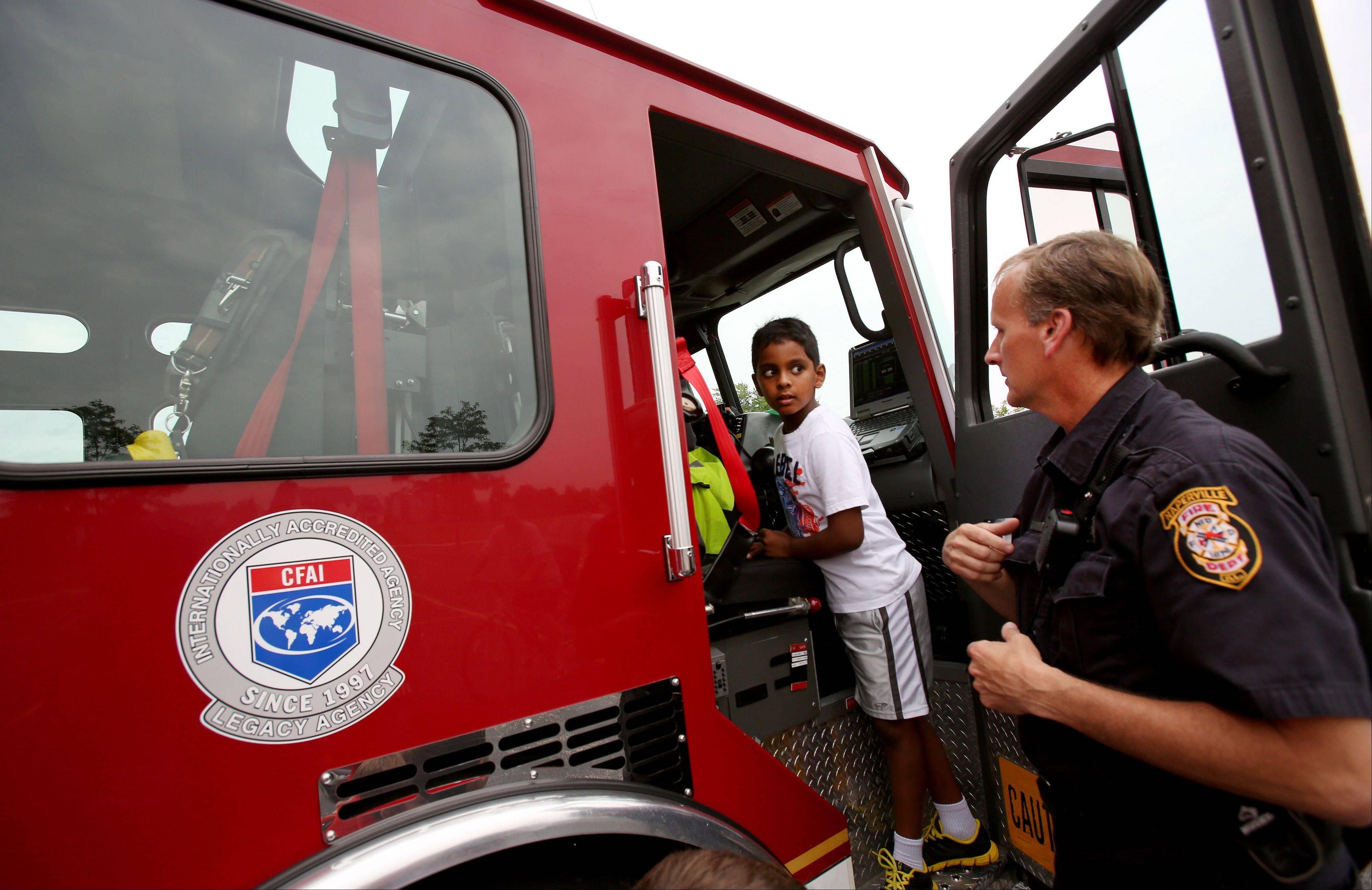 Anish Basety, 7, gets a look inside a fire truck, with the help of firefighter/paramedic Bob Holliger during National Night Out in Naperville in the High Meadow subdivision.