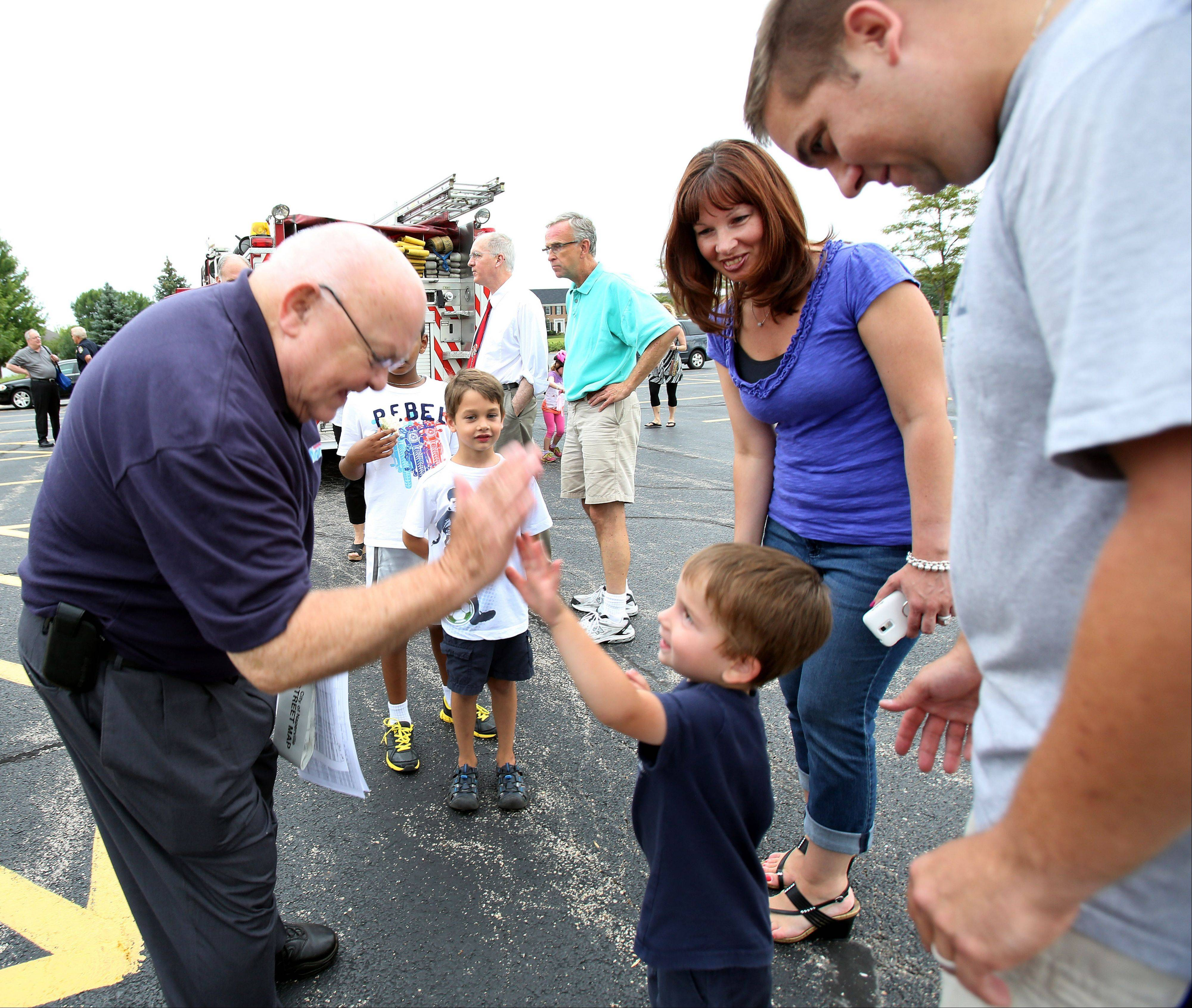 Mayor George Pradel gives a high-five to Chase Accardi, 3, with his parents Joe and Lisa Accardi, during National Night Out in Naperville in the High Meadow subdivision.