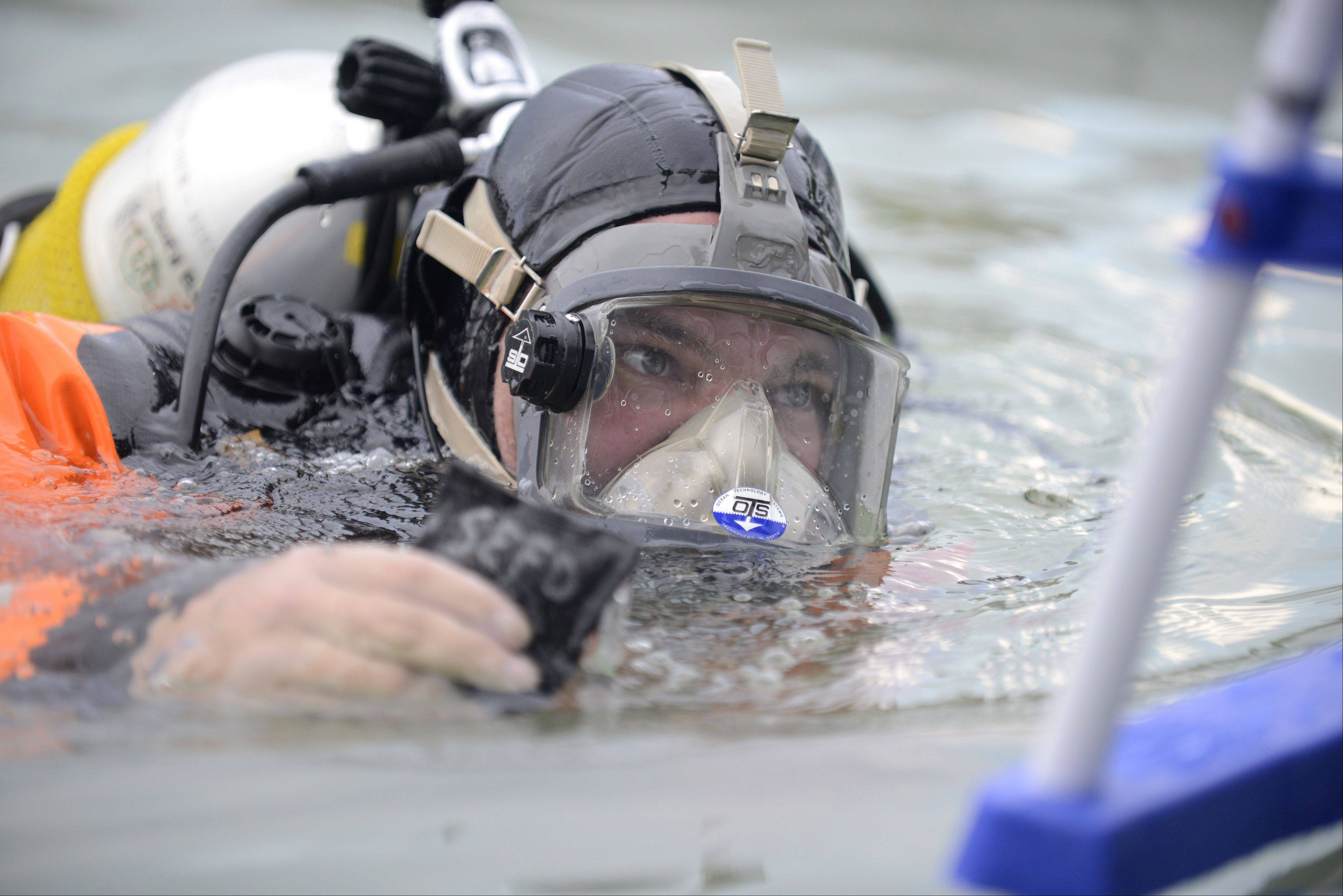 Scott Diehl, a South Elgin fire fighter/paramedic and member of the dive team, brings a retrieved weight out of the water during an interactive dive exercise with the public at South Elgin's National Night Out event in Concord Park on Tuesday, August 6.