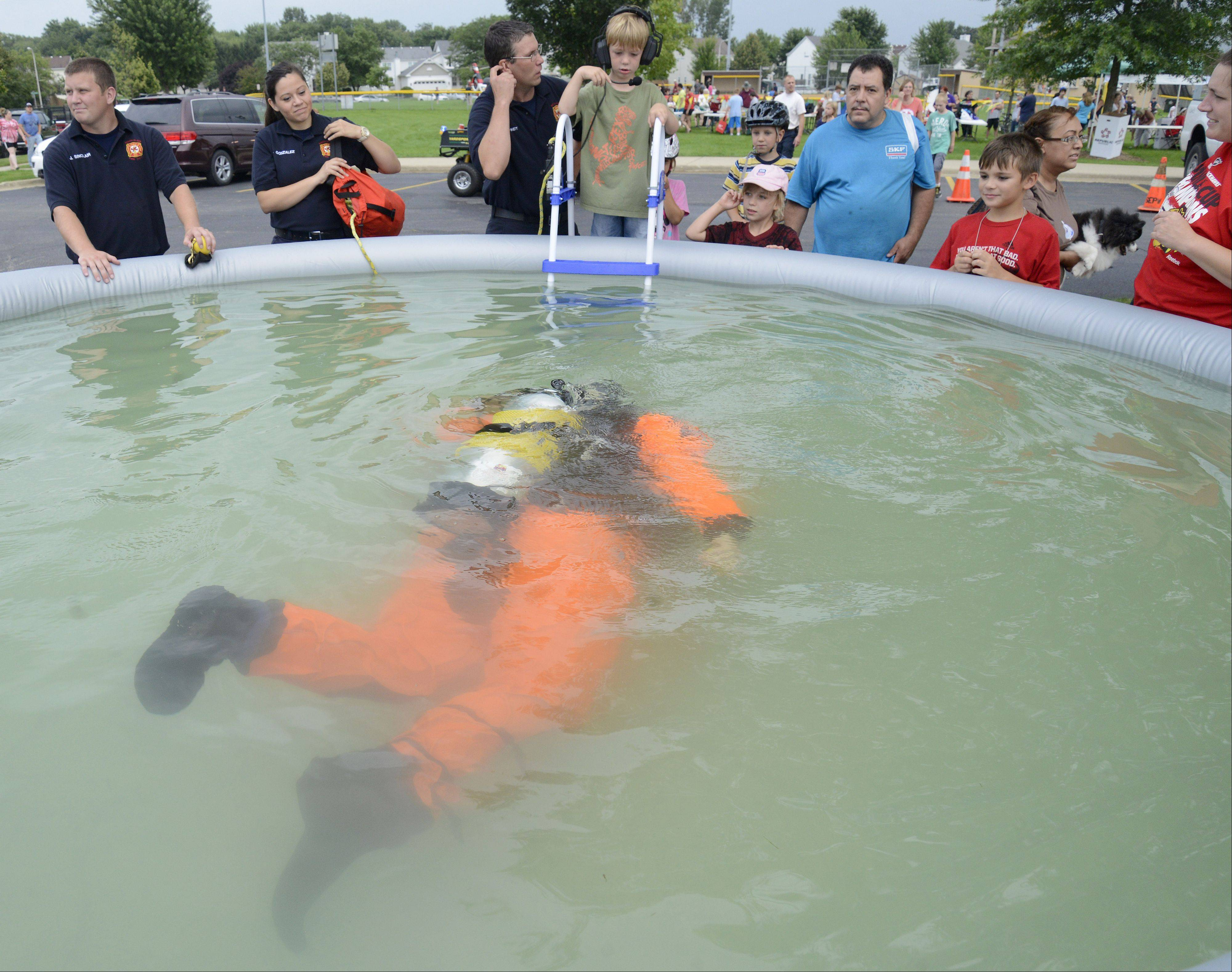 Scott Diehl, a South Elgin fire fighter/paramedic and member of the dive team, brings a retrieved weight from the bottom of the pool to Davin Birkett, 5, and his father, South Elgin fire fighter/paramedic and team diver, Ray Birkett, at South Elgin's National Night Out event in Concord Park on Tuesday, August 6. Davin spoke through a headphone system directing Diehl to find the weight in the cloudy water.