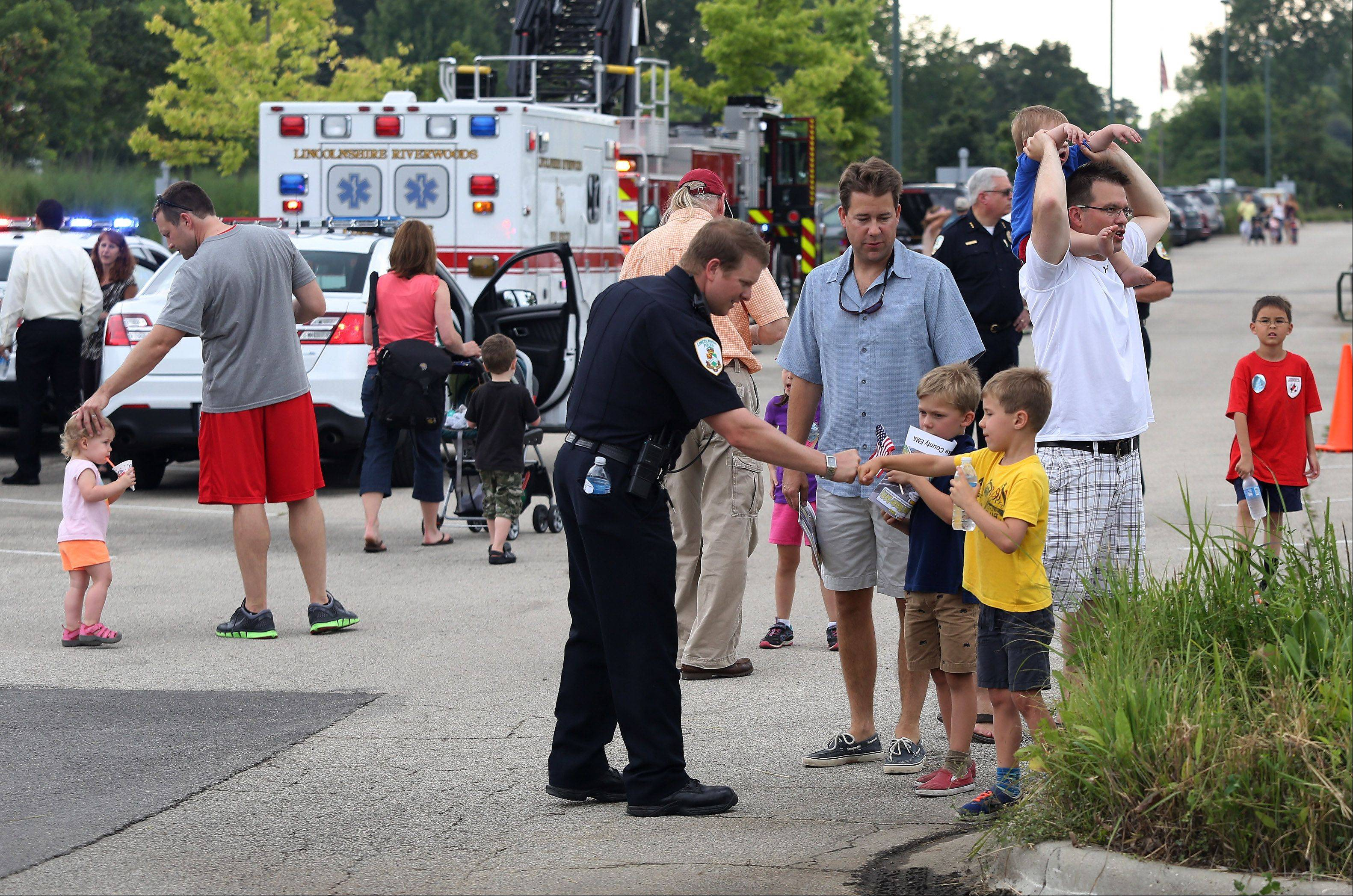 Lincolnshire Police Ofc. Brian Balinski greets twins David and Brad Simmons, 7, during the Lincolnshire National Night Out Tuesday at North Park. The event offered child identification cards, mock crime scenes, police dog demonstrations, a chance to see a Flight For Life helicopter and more.