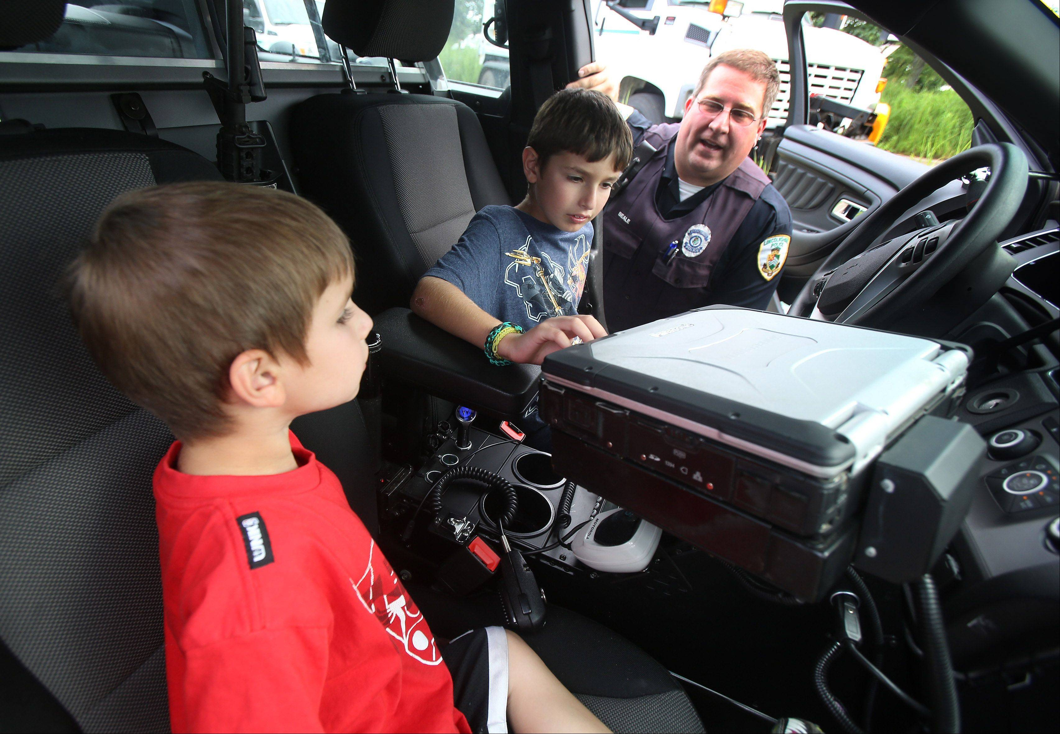 Lincolnshire Police Ofc. T. J. Beale describes the interior of a police car with Josh Cohen, 8, and his brother, Dylan, 4, of Buffalo Grove during the Lincolnshire National Night Out Tuesday at North Park. The event offered child identification cards, mock crime scenes, police dog demonstrations, a chance to see a Flight For Life helicopter and more.