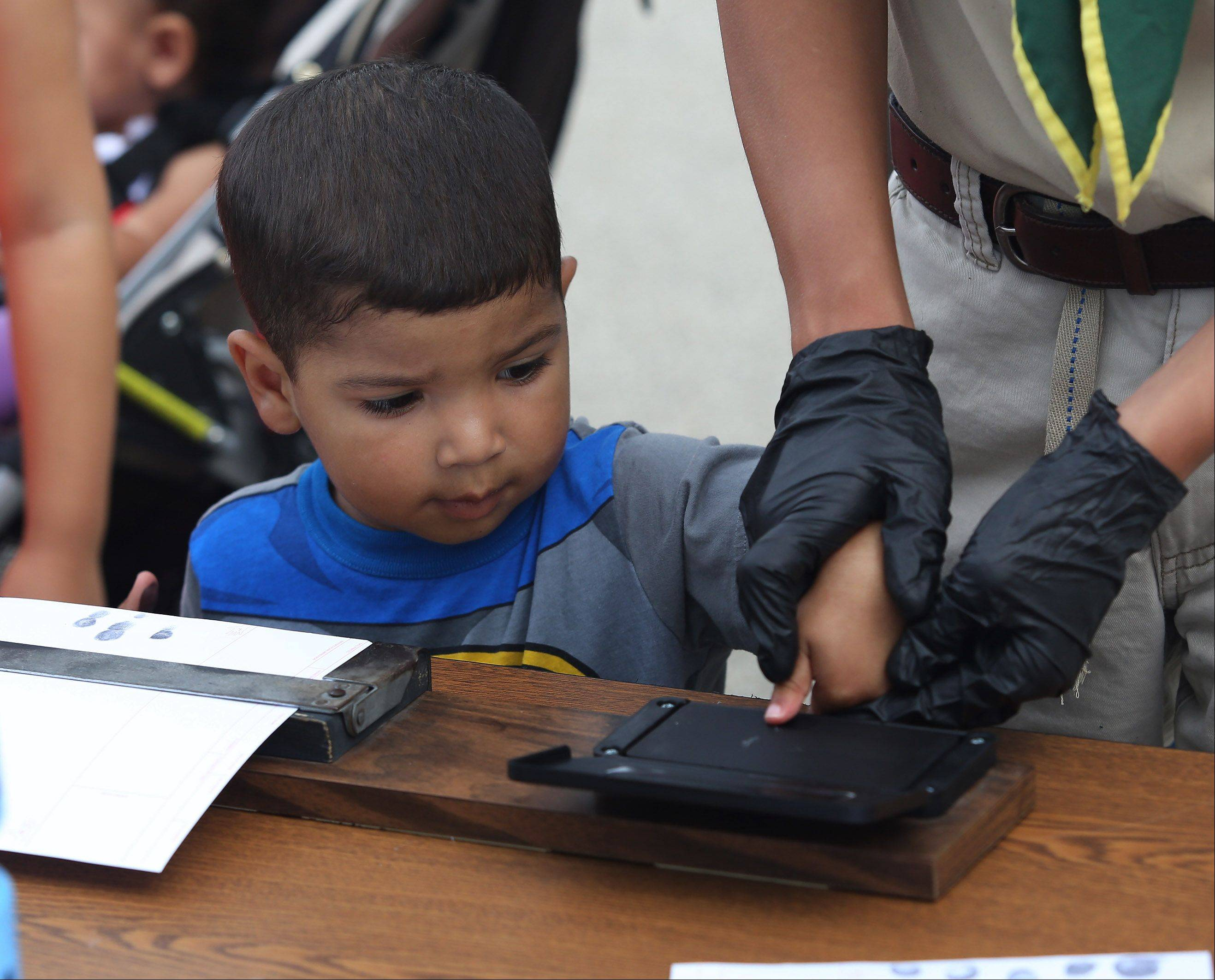James Bonner, 3, watches as he is fingerprinted by a Boy Scout from Troop 78 during the Lincolnshire National Night Out Tuesday at North Park. The event offered child identification cards, mock crime scenes, police dog demonstrations, a chance to see a Flight For Life helicopter and more.