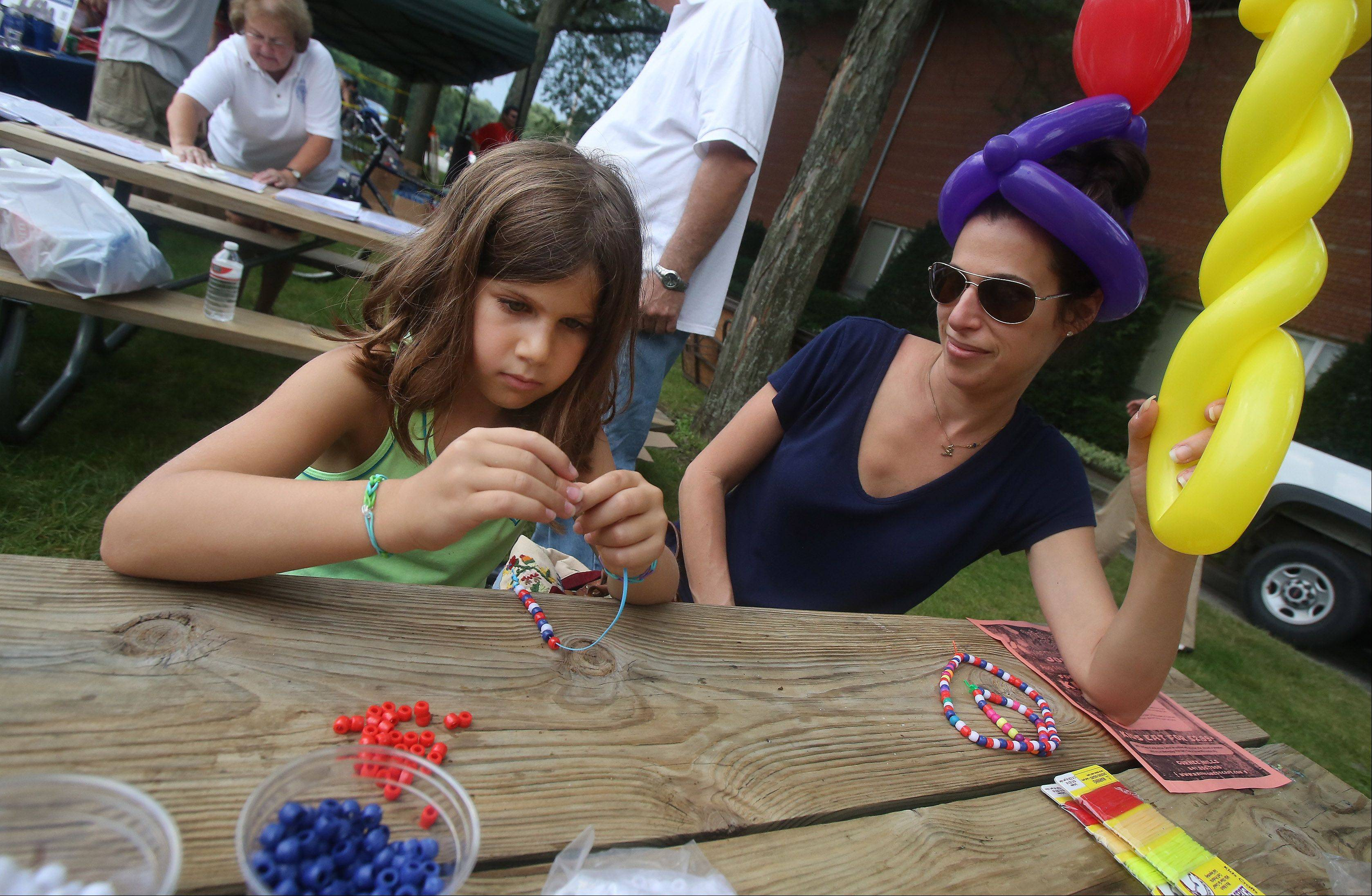 Mundelein residents Sophie Hammer, 6, makes a bead necklace with her mom, Laura, during the Mundelein National Night Out Tuesday at Kracklauer Park. The event offered a dunk tank, games, food, a chance to meet police officers and more.