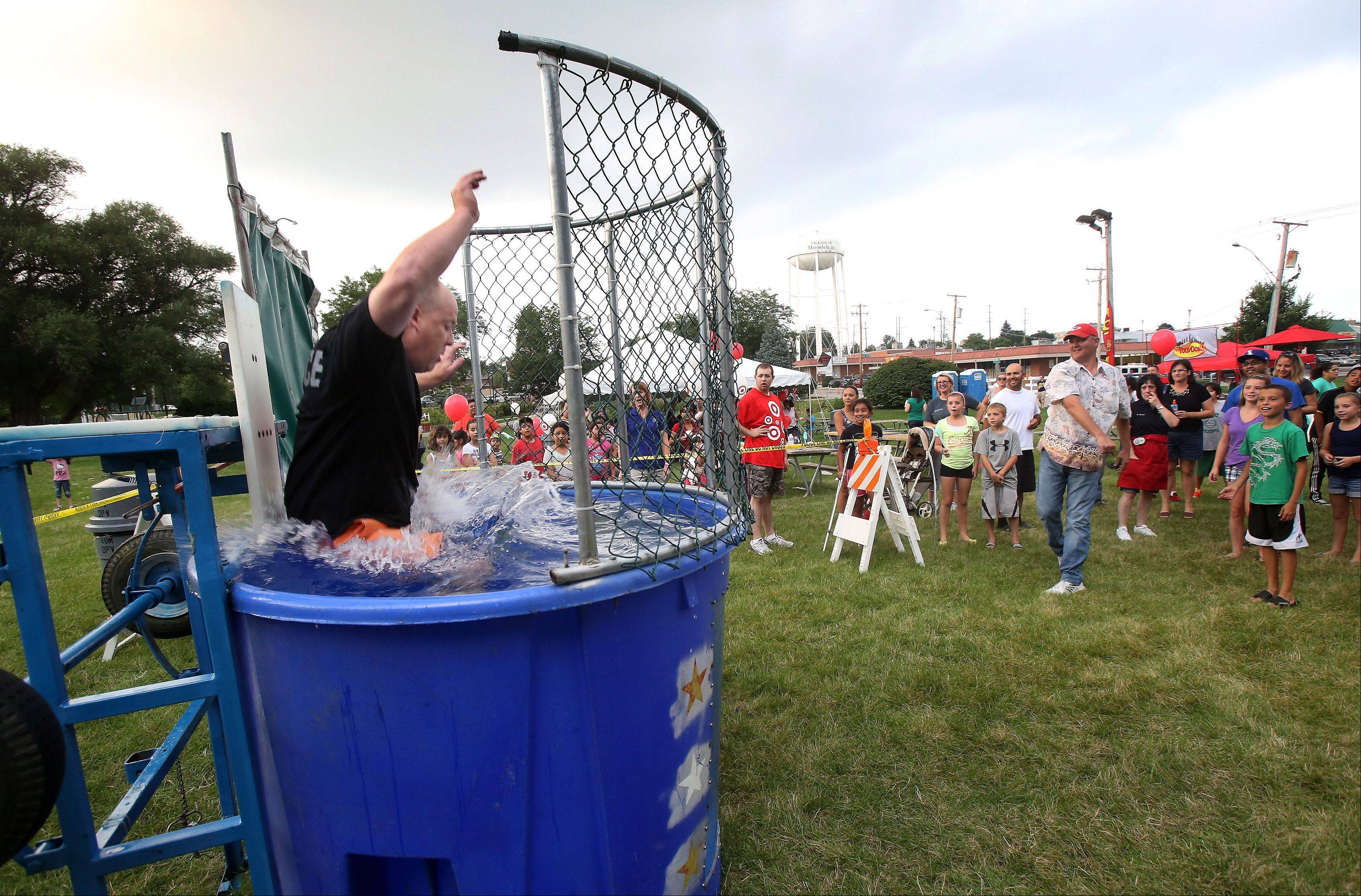 Mundelein Police Chief Eric Guenther is knocked in the water in the dunk tank during the Mundelein National Night Out Tuesday at Kracklauer Park. The event offered a dunk tank, games, food, a chance to meet police officers and more.