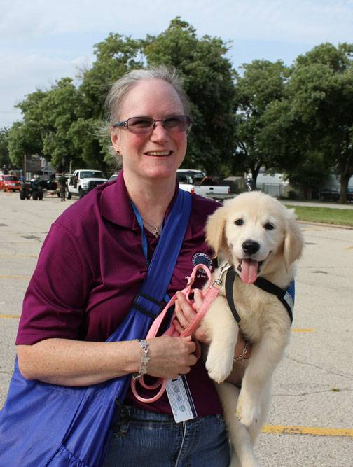 Mary Trapp, Lutheran Church Charities, holds Golden Retriever puppy Shiloh, a comfort dog, at the Des Plaines Police Department's National Night Out. �Comfort dogs are brought in to assist during emergency situations.