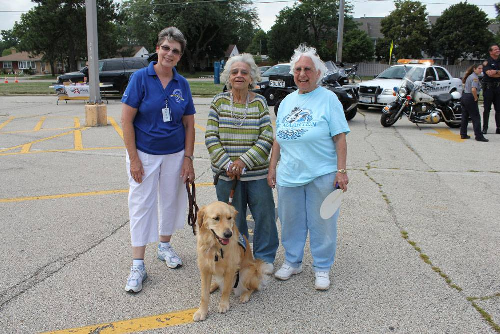 Pictured left to right�, Janice Wissert, Handler for the Lutheran Church Charities Comfort Dogs, Helen Rzeczkowski, Des Plaines resident of 61 years, and Joan Potempa, 64 year resident of Des Plaines Illinois, pose for a photograph at the National Night Out, the annual event sponsored by the Des Plaines Police Department. �Kids of all ages enjoyed the comfort dogs.�