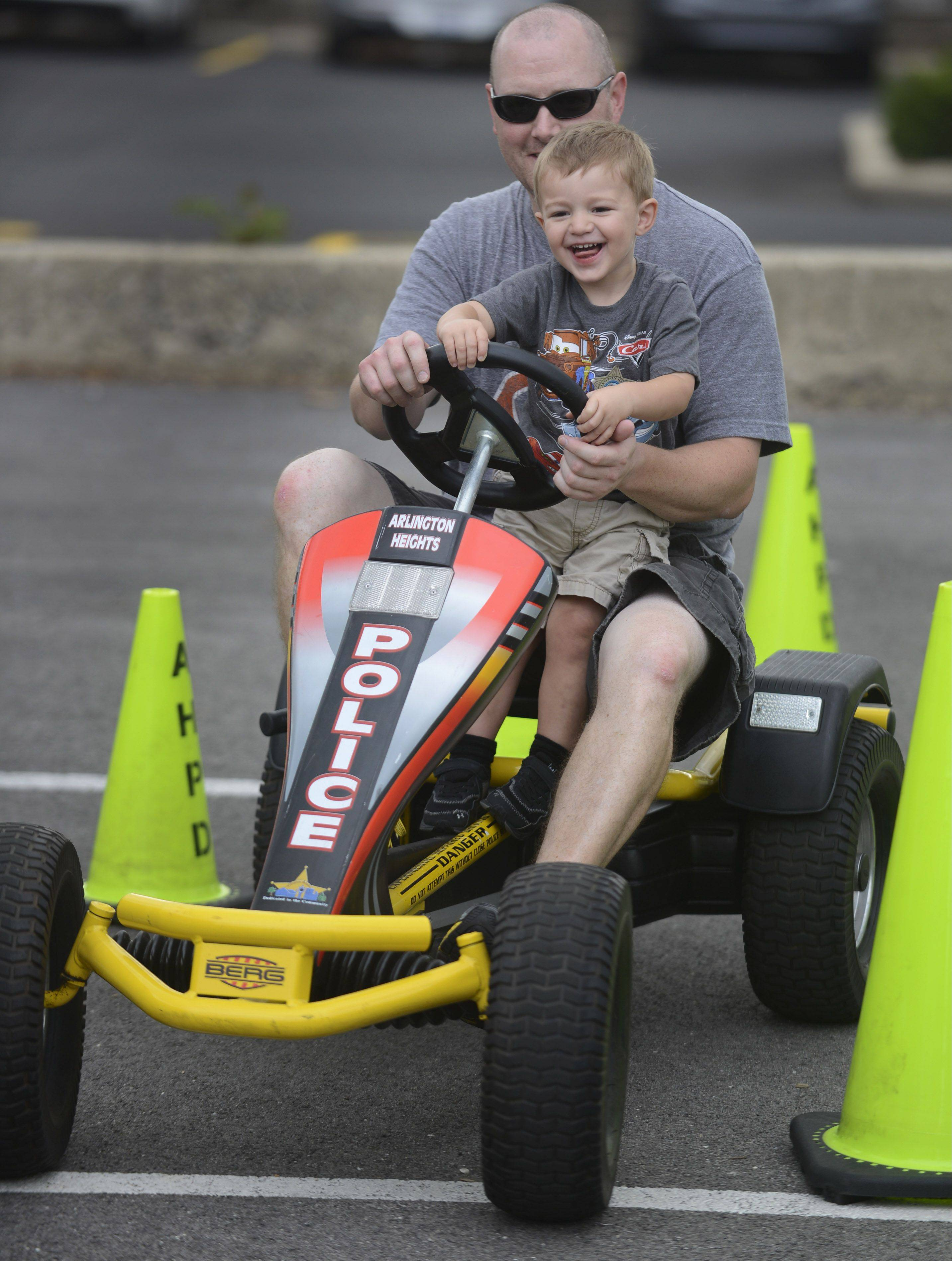 Off-duty Arlington Heights Police Officer Brian Brosnan gives his son Mason a spin in a pedal car used to demonstrate the effects of impaired driving during the Arlington Heights National Night Out at North School Park Tuesday.