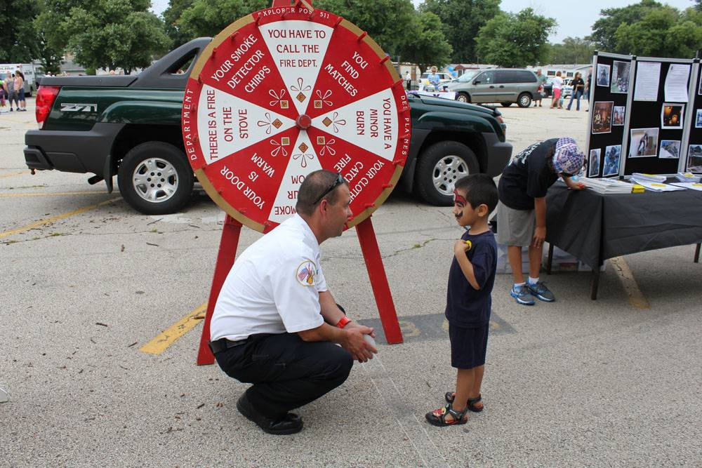 Left to right, Des Plaines Firefighter Jim Utinans discusses safety and fire prevention with Gary Caceres at National Night Out.�
