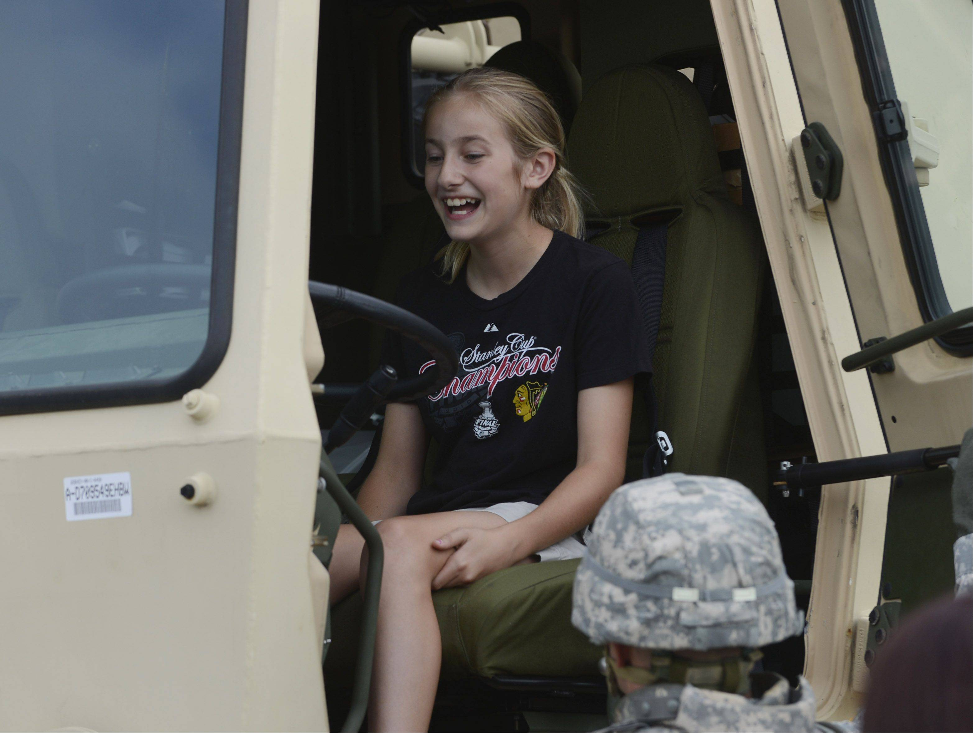 Jamie Siebert, 11, of Arlington Heights sits in an Army truck during the Arlington Heights National Night Out at North School Park Tuesday.
