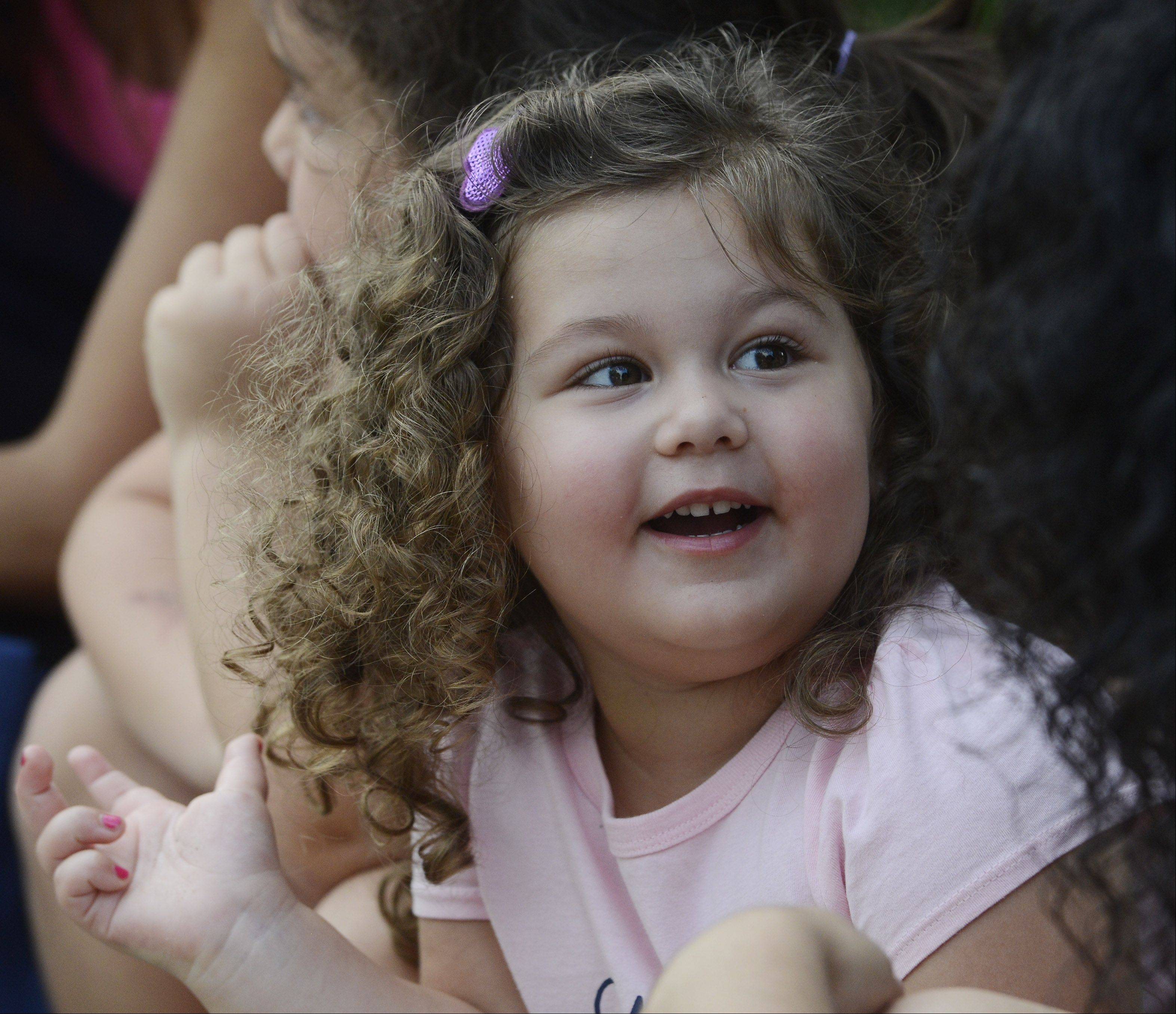 Vincenza Principato, 3, of Roselle smiles while watching the BMX bike stunt show during the Bartlett National Night Out at Bartlett Park Tuesday.