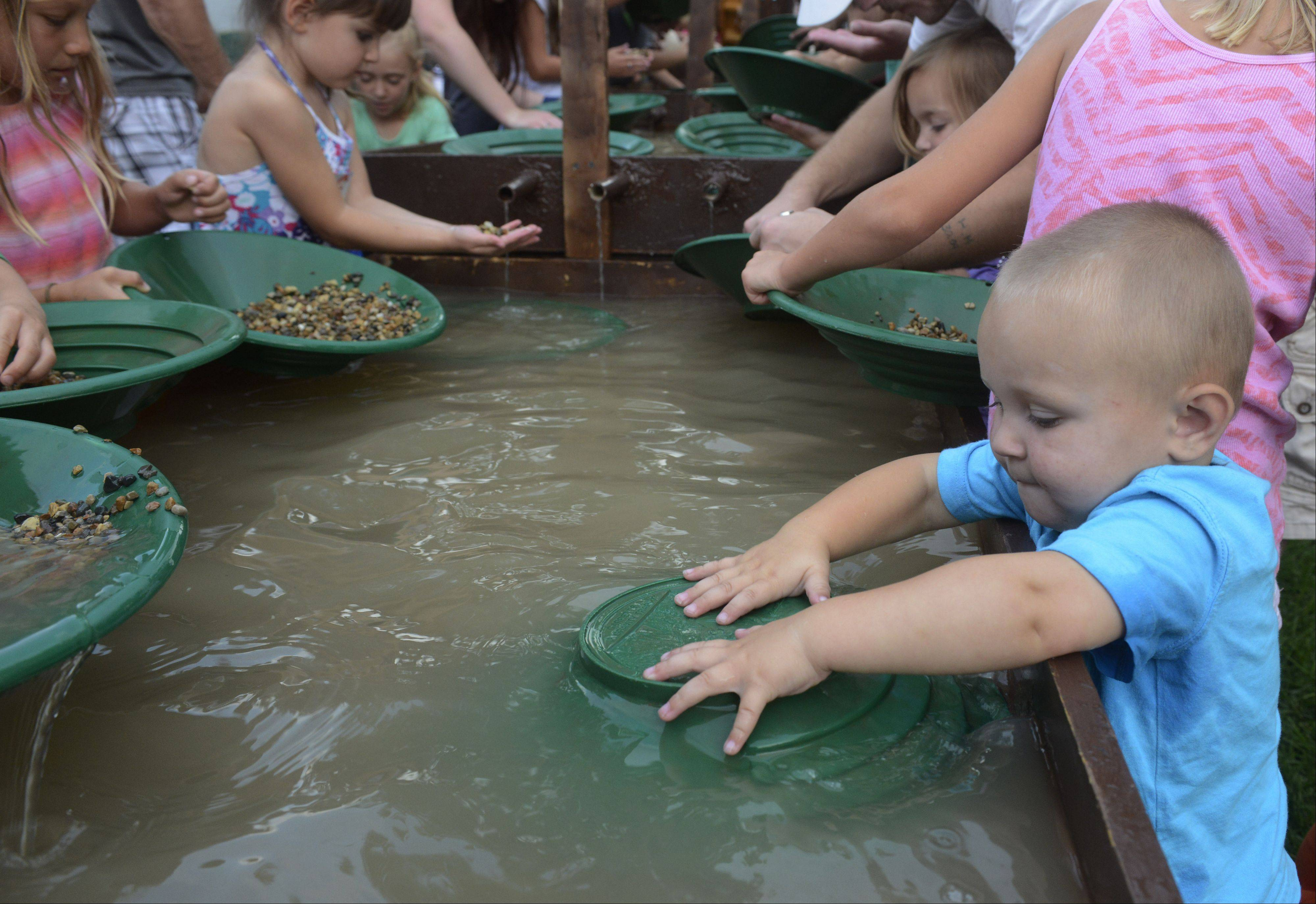 "Breyden Velna, age 1, ""pans for gold"" during the Bartlett National Night Out at Bartlett Park Tuesday."