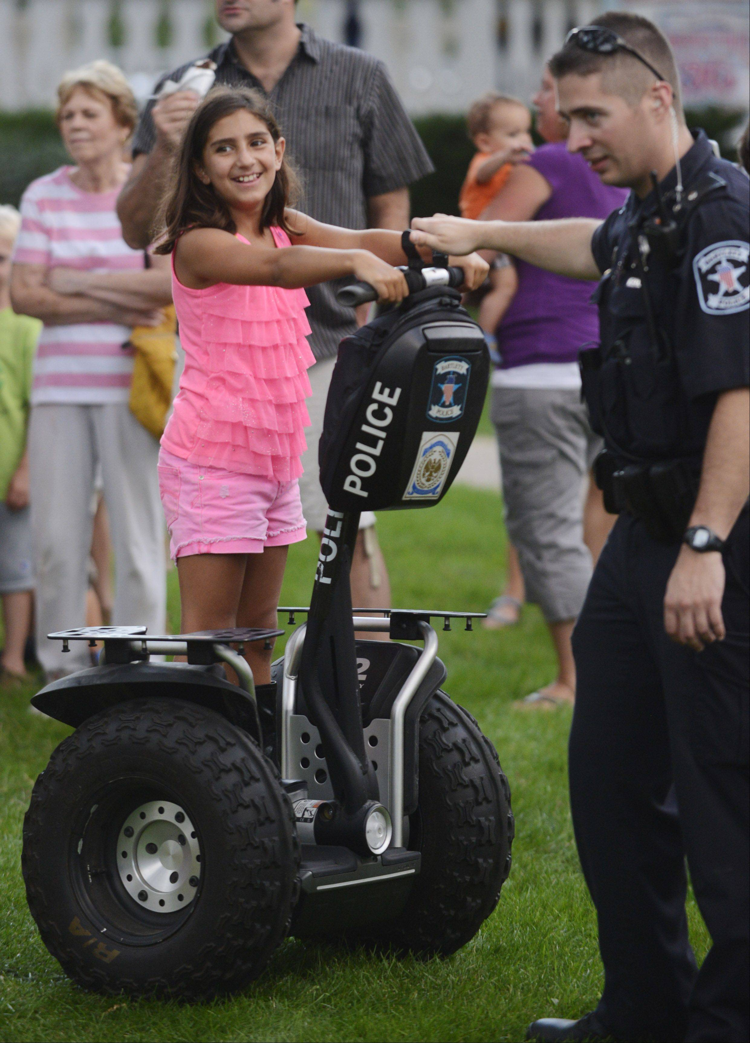 Gina Giuseffi, 9, of Bartlett rides a police Segway with the help of Officer Brian Camarata during the Bartlett National Night Out at Bartlett Park Tuesday.