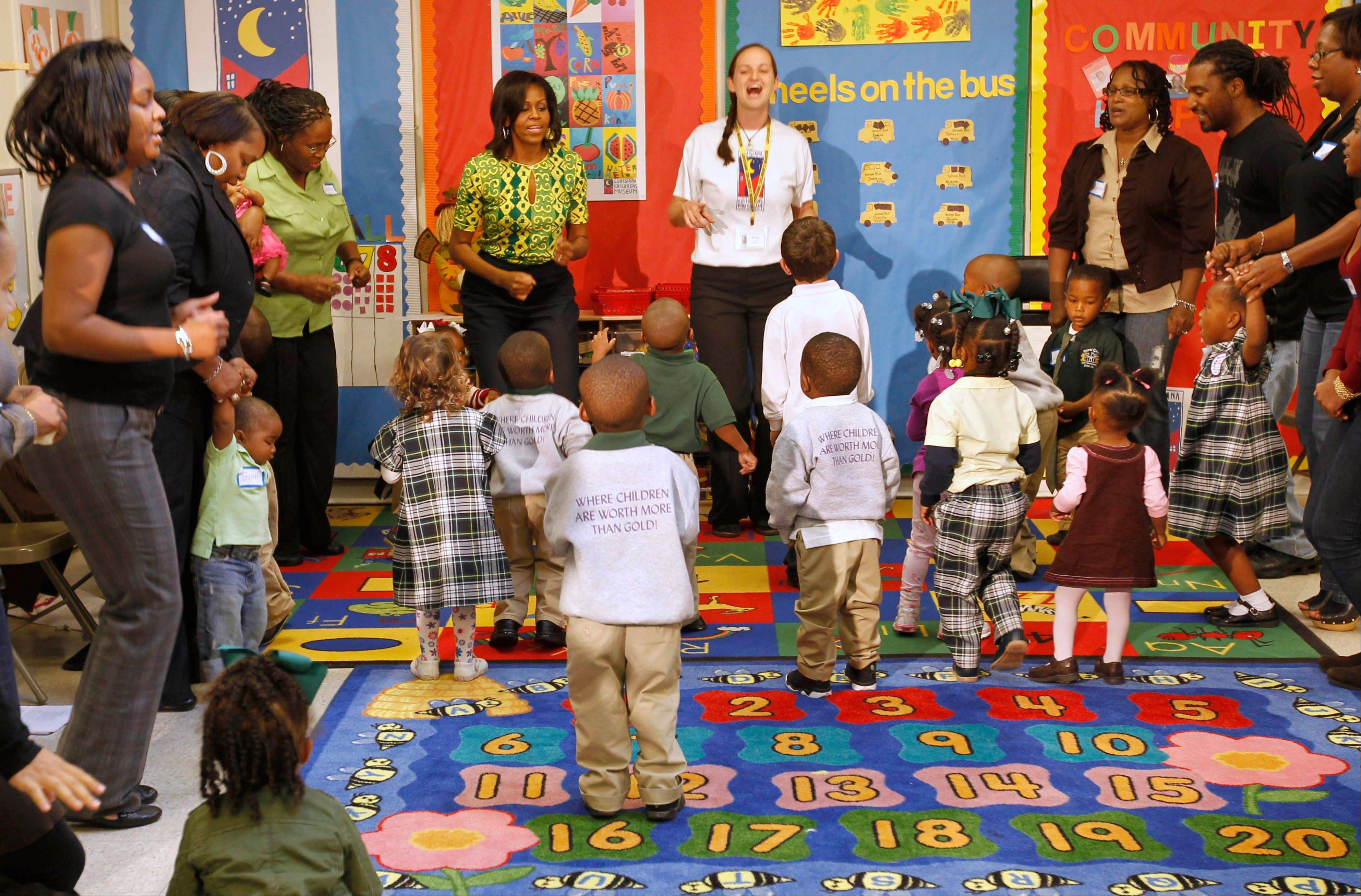 "First lady Michelle Obama sings and dances to exercises with staff, parents and children as she visits the Royal Castle Child Development Center, as part of the ""Lets Move!"" initiative in New Orleans, La."