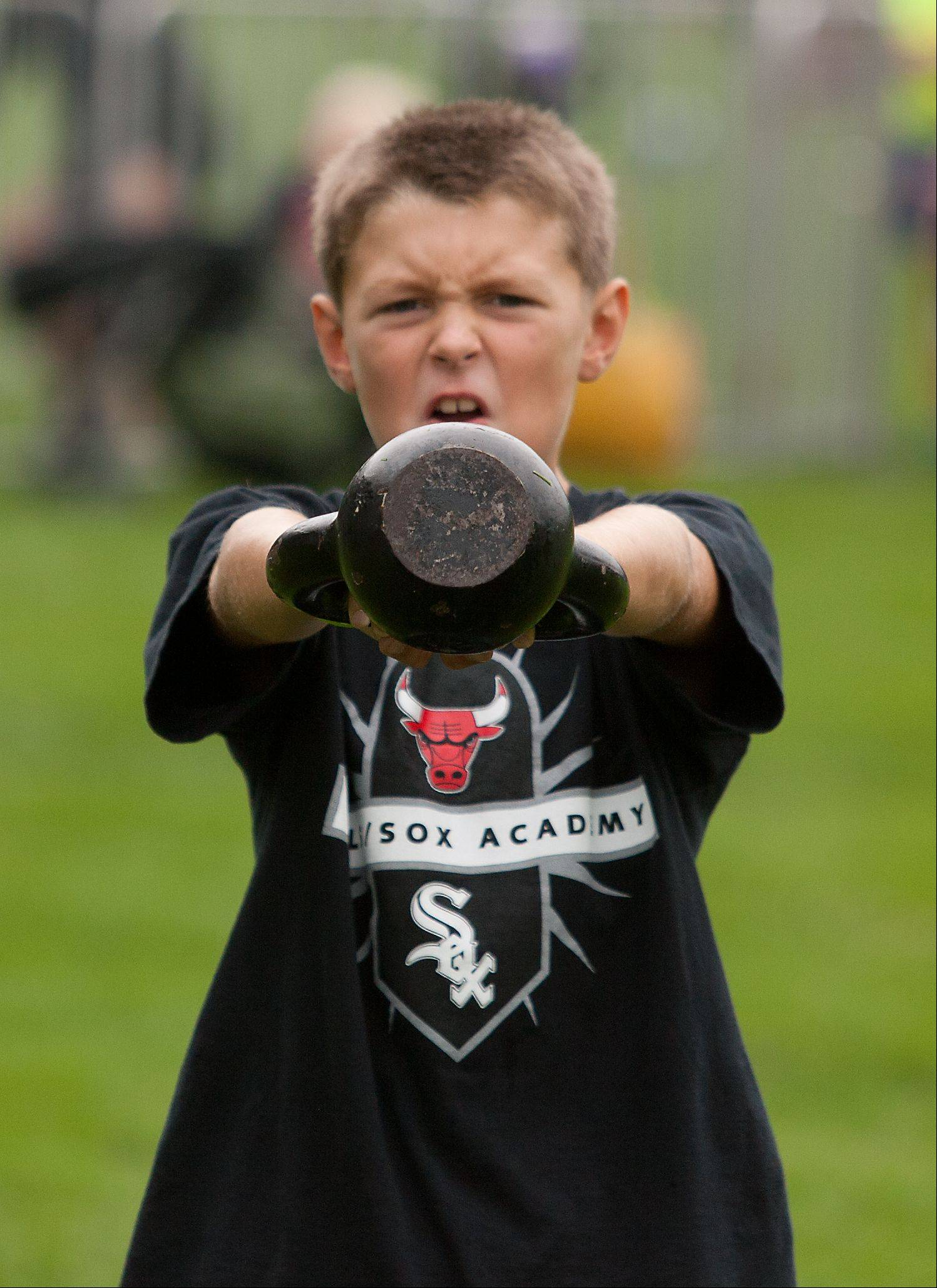 Casey Morrison, 8, of Wheaton, works with a kettle bell during the inaugural health and fitness boot camp Tuesday at Cantigny Park in Wheaton.