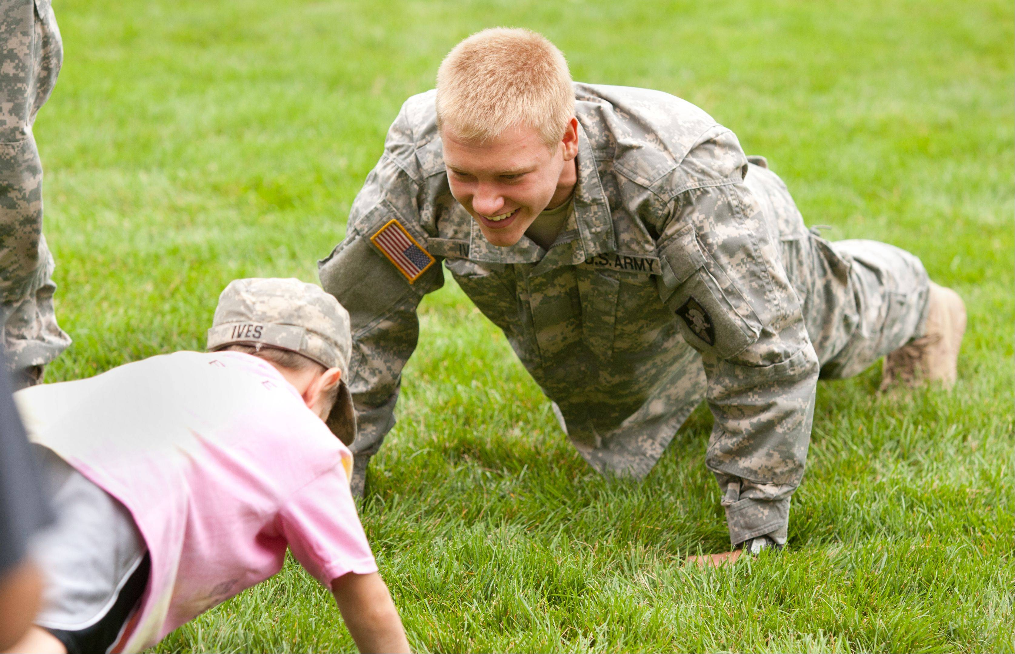 Nick Ives, a cadet at West Point, monitors pushups during Tuesday's inaugural health and fitness boot camp for children ages 3 through 12 at Cantigny Park in Wheaton.