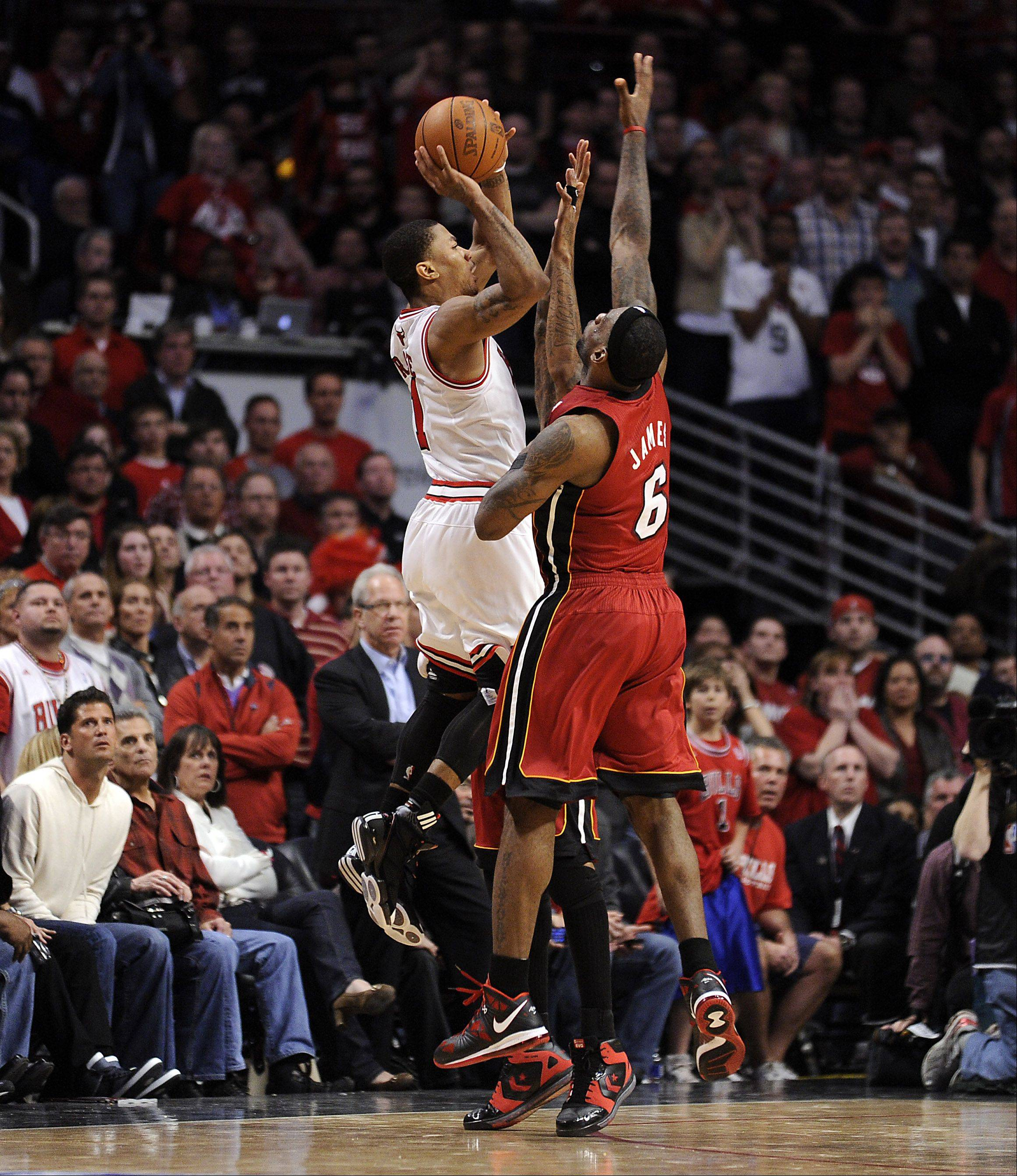 The Bulls' Derrick Rose attempts a last-second shot that the Heat's LeBron James blocks.