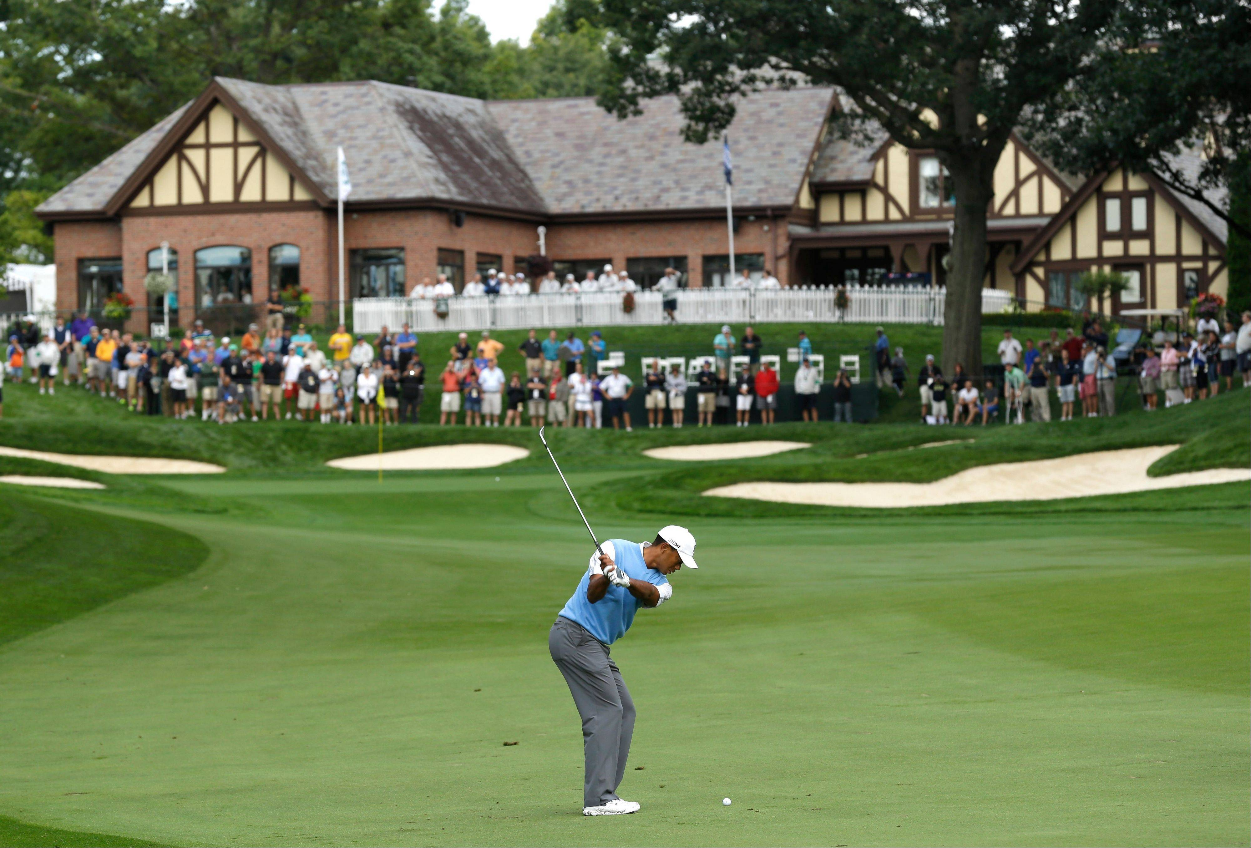 Tiger Woods hits to the 18th green during a practice round for the PGA Championship golf tournament at Oak Hill Country Club, Tuesday. Illini golf coach Mike Small again earned a spot in the field, which opens play on Thursday.