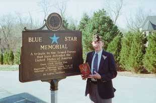 Mr. Banas displays his award-winning book while standing next to a Blue Star Memorial plaque dedicated to all who served in the U.S. Armed Forces.