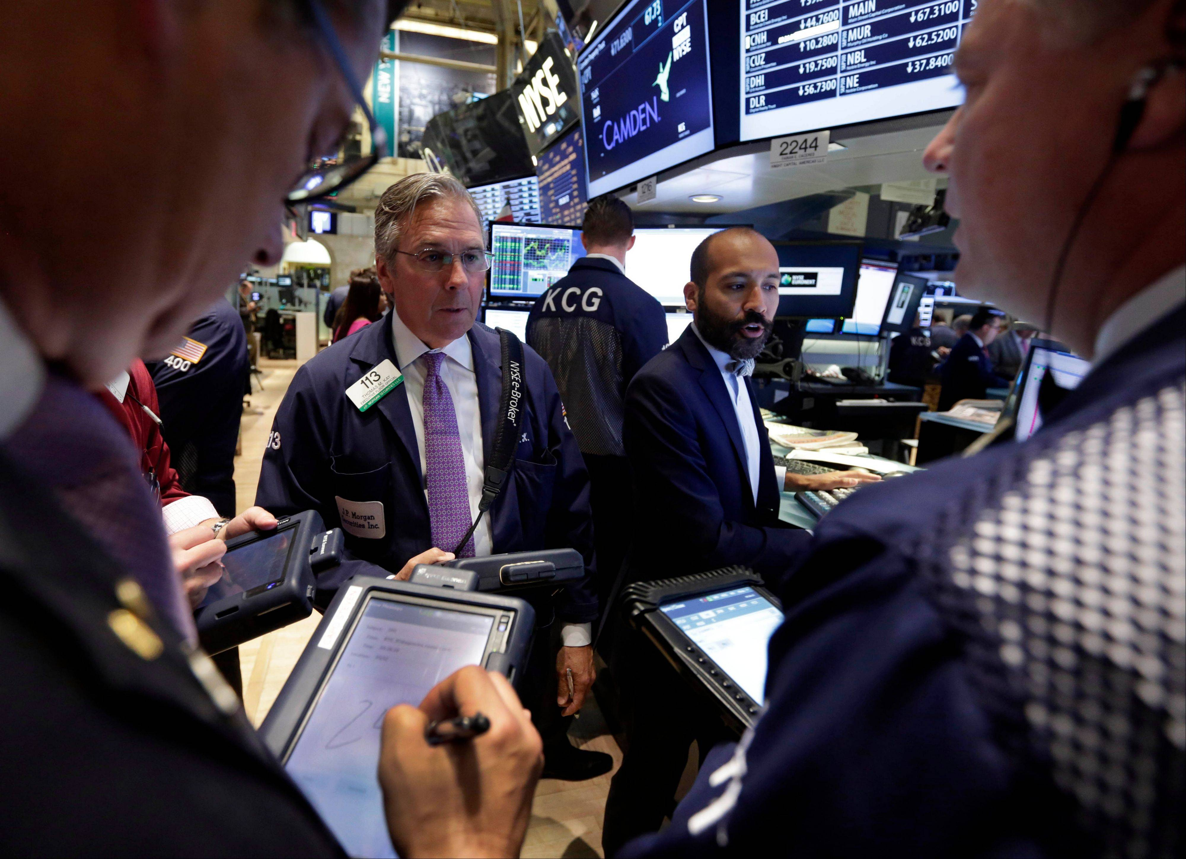 In this Wednesday, July 31, 2013, file photo, Specialist Fabian Caceres, background right, works with traders on the floor of the New York Stock Exchange. World stock markets fell Wednesday, Aug. 7, 2013 led by a plunge in Japan�s benchmark index, as expectations mounted that the U.S. central bank will begin to phase out its monetary stimulus next month.