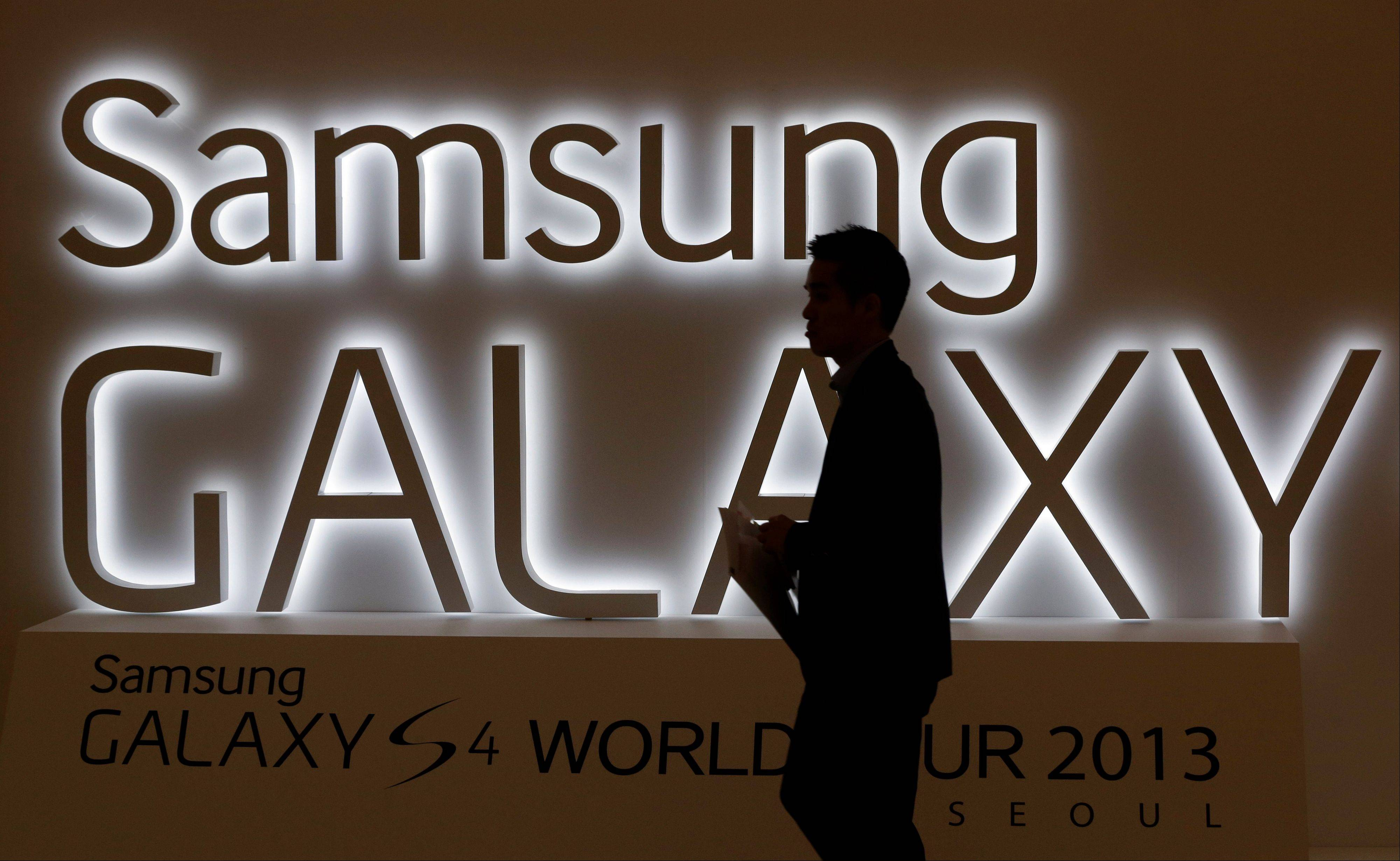 A man walks by a logo of Samsung Electronics Co.�s latest smartphone Galaxy S4 during its unveiling ceremony in Seoul, South Korea. Samsung Electronics Co. has applied for U.S. and South Korean trademarks for a watch that connects to the Internet in the latest sign that consumer technology companies see wearable devices as the future of their business.