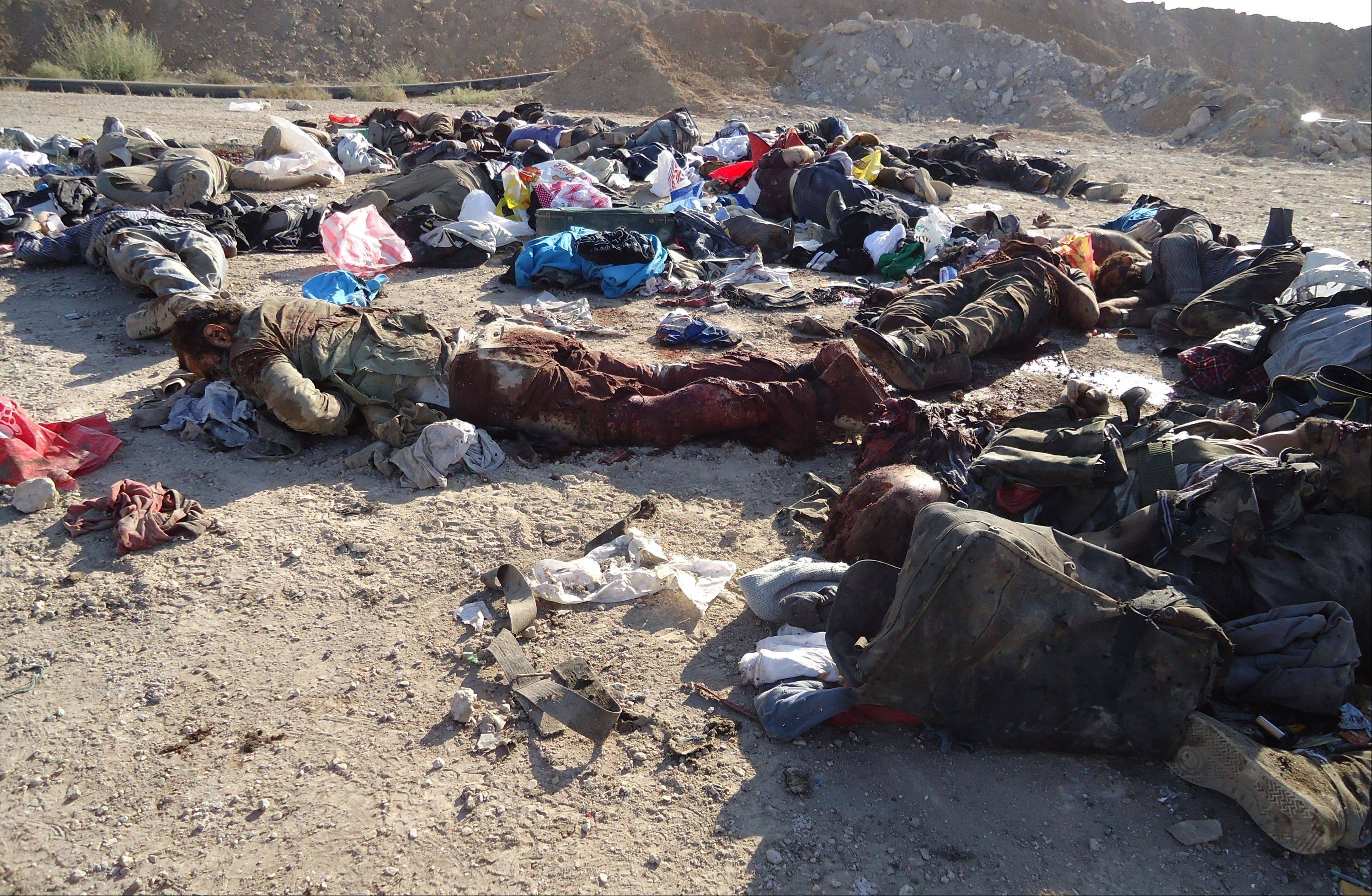 In this photo released by the Syrian official news agency SANA, dead bodies of Syrian rebels are seen on the ground, killed during ambush by Syrian forces near the Damascus suburb of Adra, Syria, Wednesday Aug. 7, 2013. Syrian government forces killed more than 60 rebels Wednesday in an ambush near Damascus, a blow to opposition fighters confronting a regime offensive in the capital, activists said.