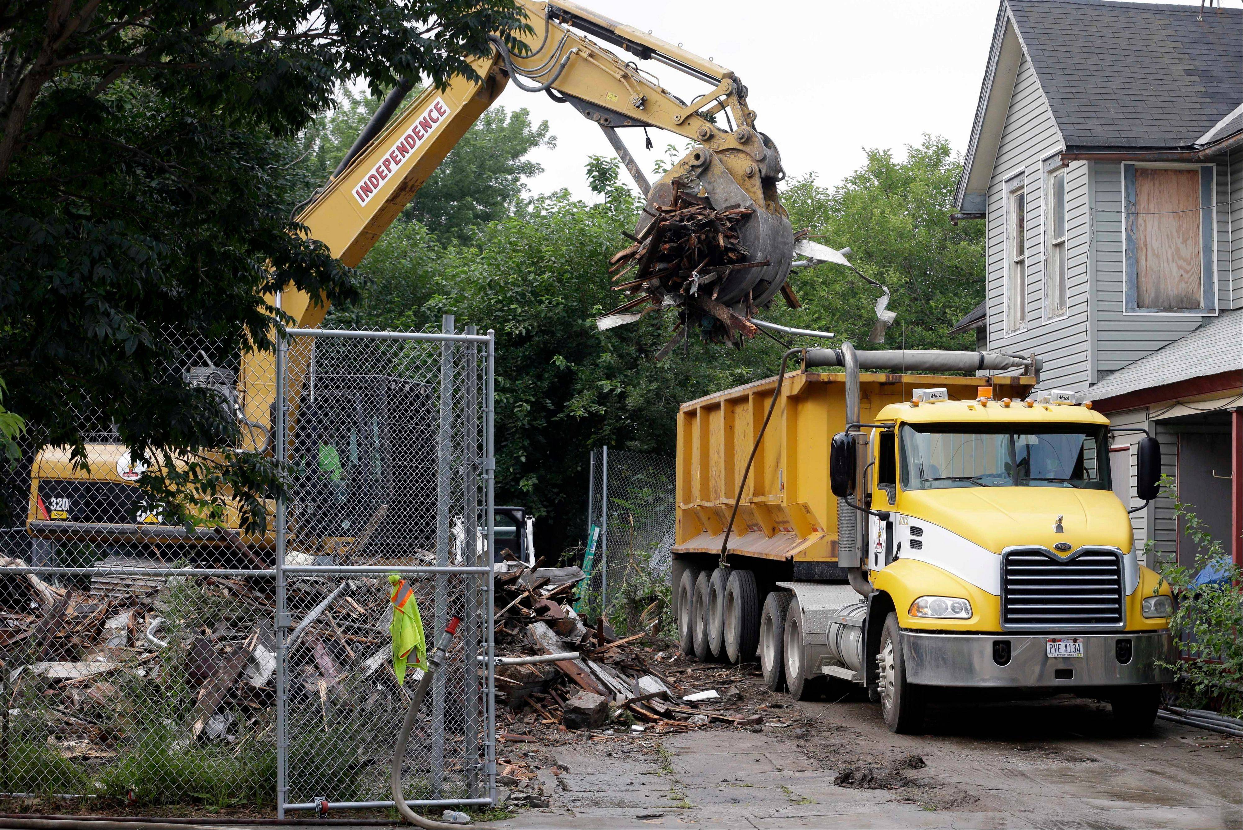 Debris is loaded onto a truck at a house where three women were held captive and raped for more than a decade, Wednesday, Aug. 7, 2013, in Cleveland. Authorities want to make sure the rubble isn�t sold online as �murderabilia,� though no one died there. The house was torn down as part of a deal that spared Ariel Castro a possible death sentence. He was sentenced last week to life in prison plus 1,000 years. He apologized but blamed his addiction to pornography.