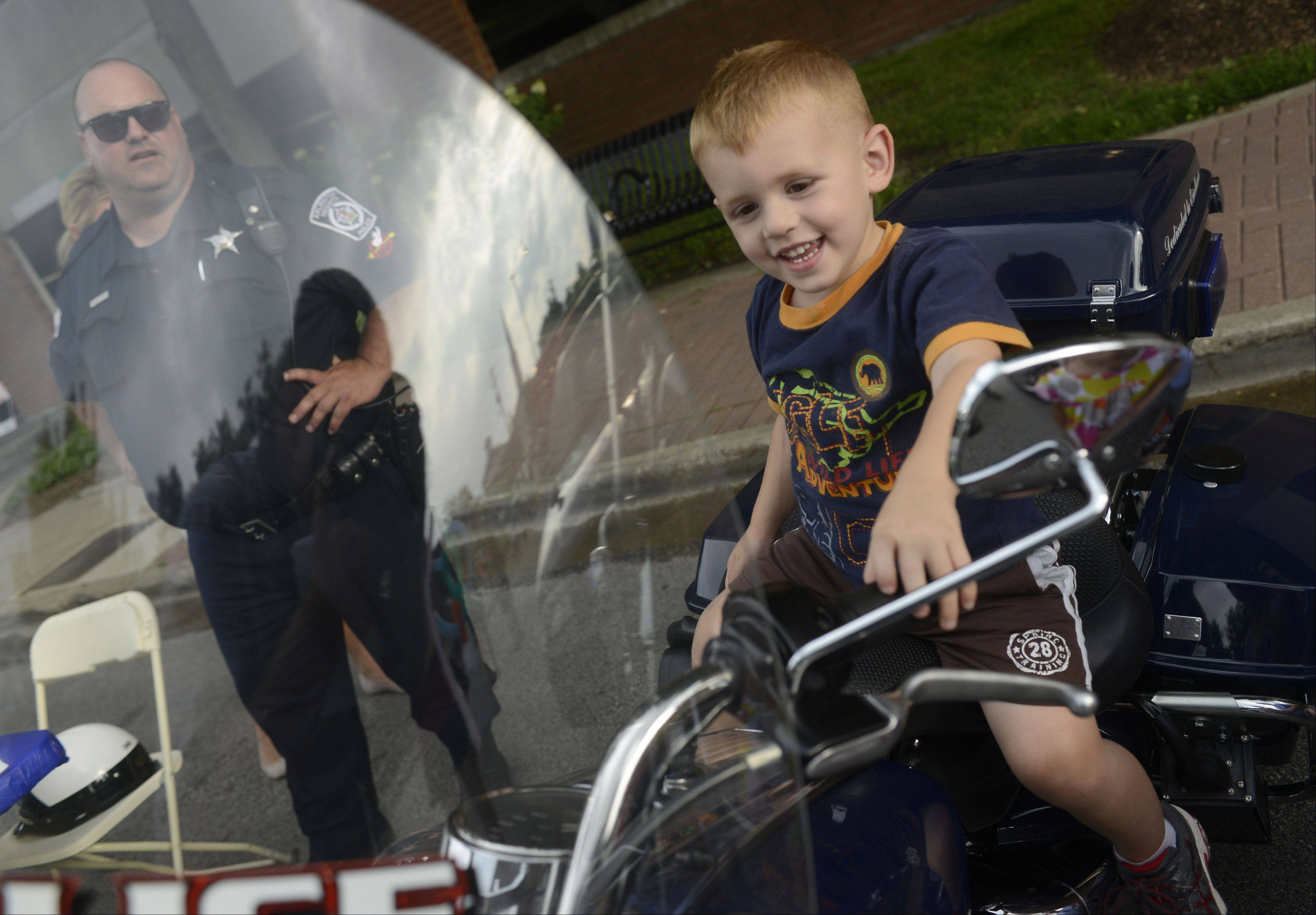 Pax Stukenberg, age 2�, of Arlington Heights sits on officer Tom Henderson�s police motorcycle during the Arlington Heights National Night Out at North School Park yesterday.