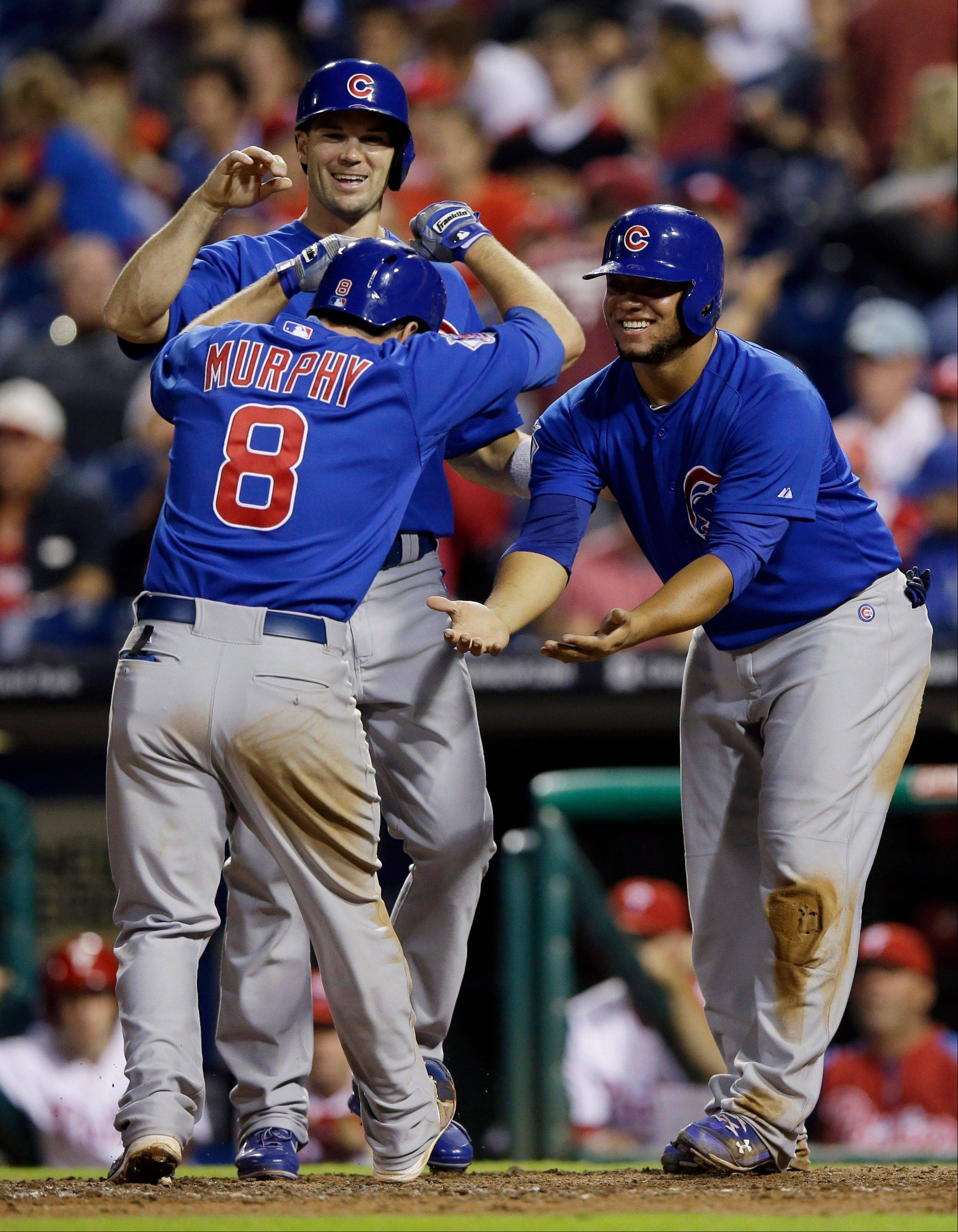 Chicago Cubs' Donnie Murphy, center, celebrates with Cole Gillespie, left, and Welington Castillo after Murphy's three-run home run during the ninth inning of a baseball game against the Philadelphia Phillies, Wednesday, Aug. 7, 2013, in Philadelphia. Chicago won 5-2. (AP Photo/Matt Slocum)