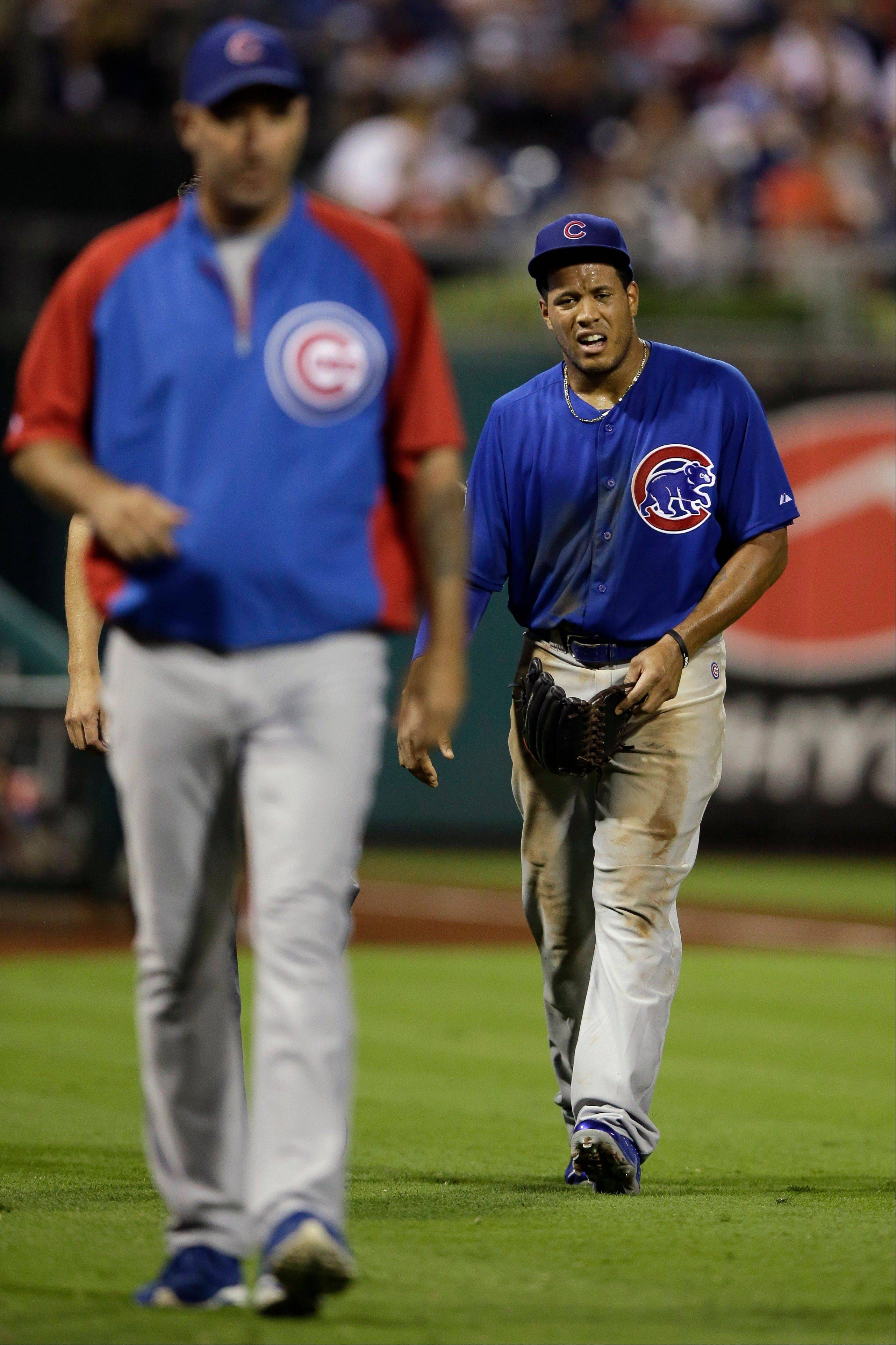 Chicago Cubs' Thomas Neal, right, walks off the field after an injury during the seventh inning of a baseball game against the Philadelphia Phillies, Wednesday, Aug. 7, 2013, in Philadelphia. (AP Photo/Matt Slocum)