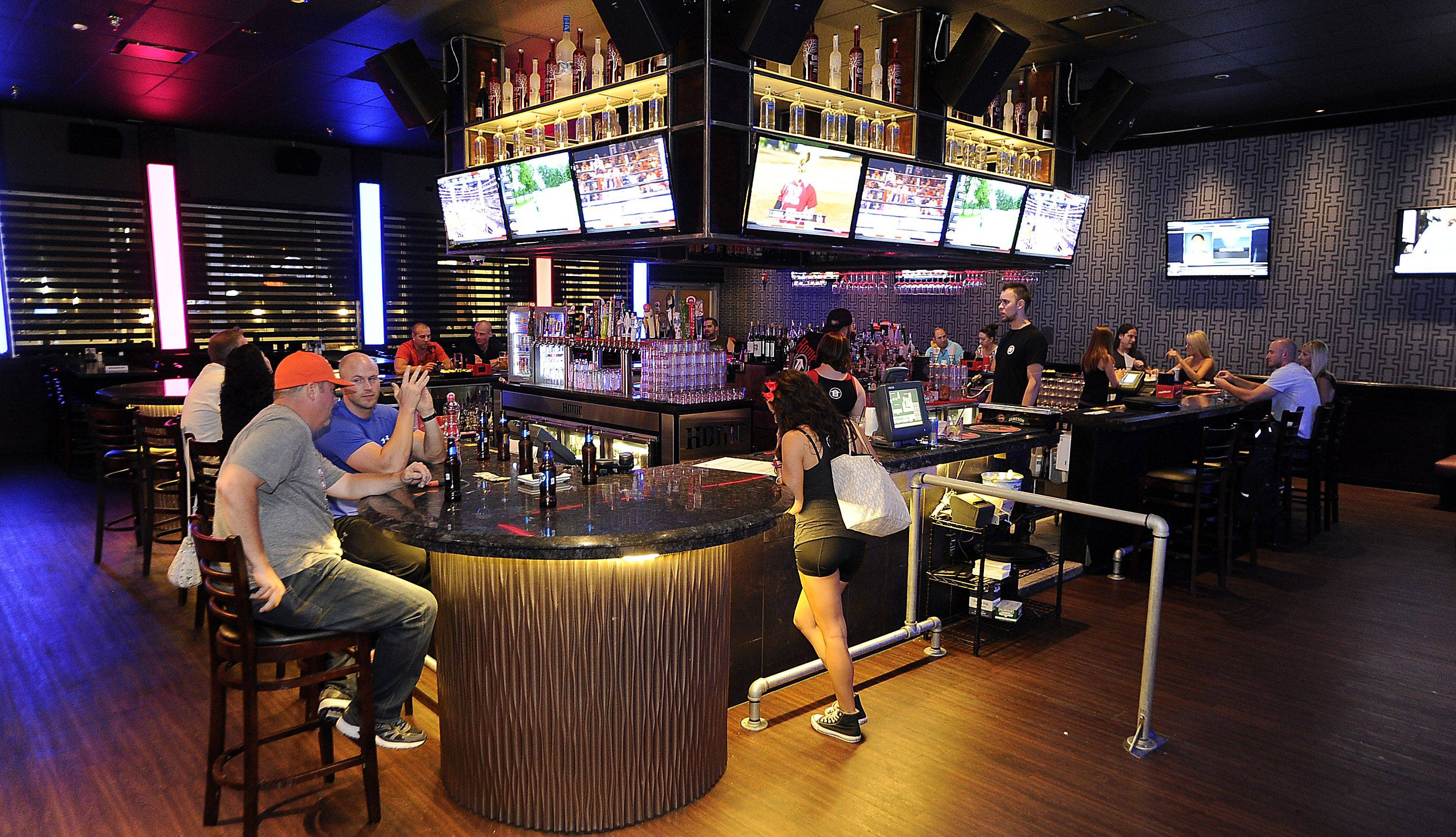 TVs line the sports bar area, above, of the House of Music & Entertainment, while bar manager Tony Herman, right, mixes up a few drinks