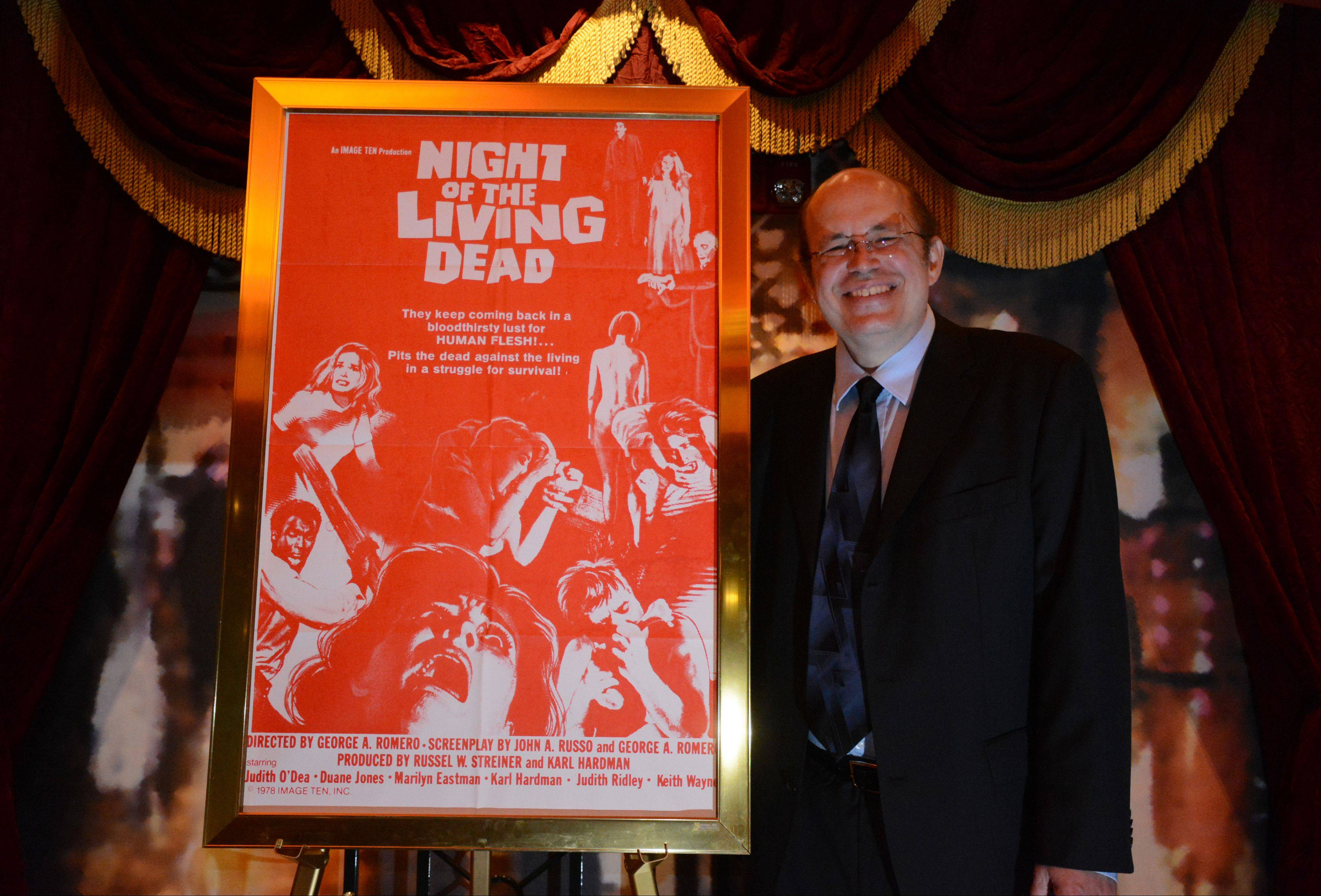"Mike Kerz, founder of Flashback Weekend, poses with his original theatrical poster for ""Night of the Living Dead."" George A. Romero, who directed the film, is a special guest at this year's convention."