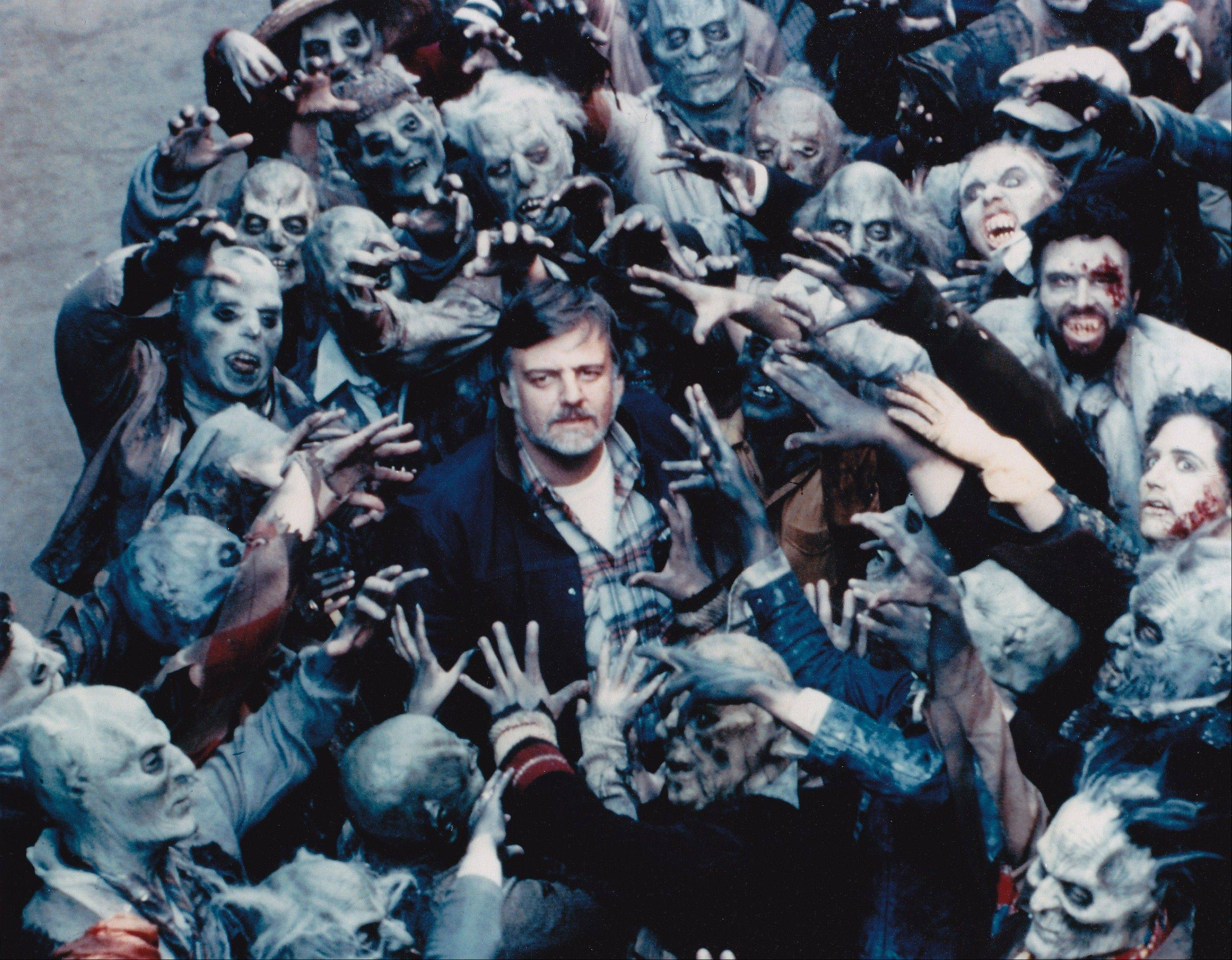 "Director George A. Romero, center, circa 1984, is mobbed by zombies on the set of ""Day of the Dead."" Romero will be at Flashback Weekend, a horror convention in Rosemont."