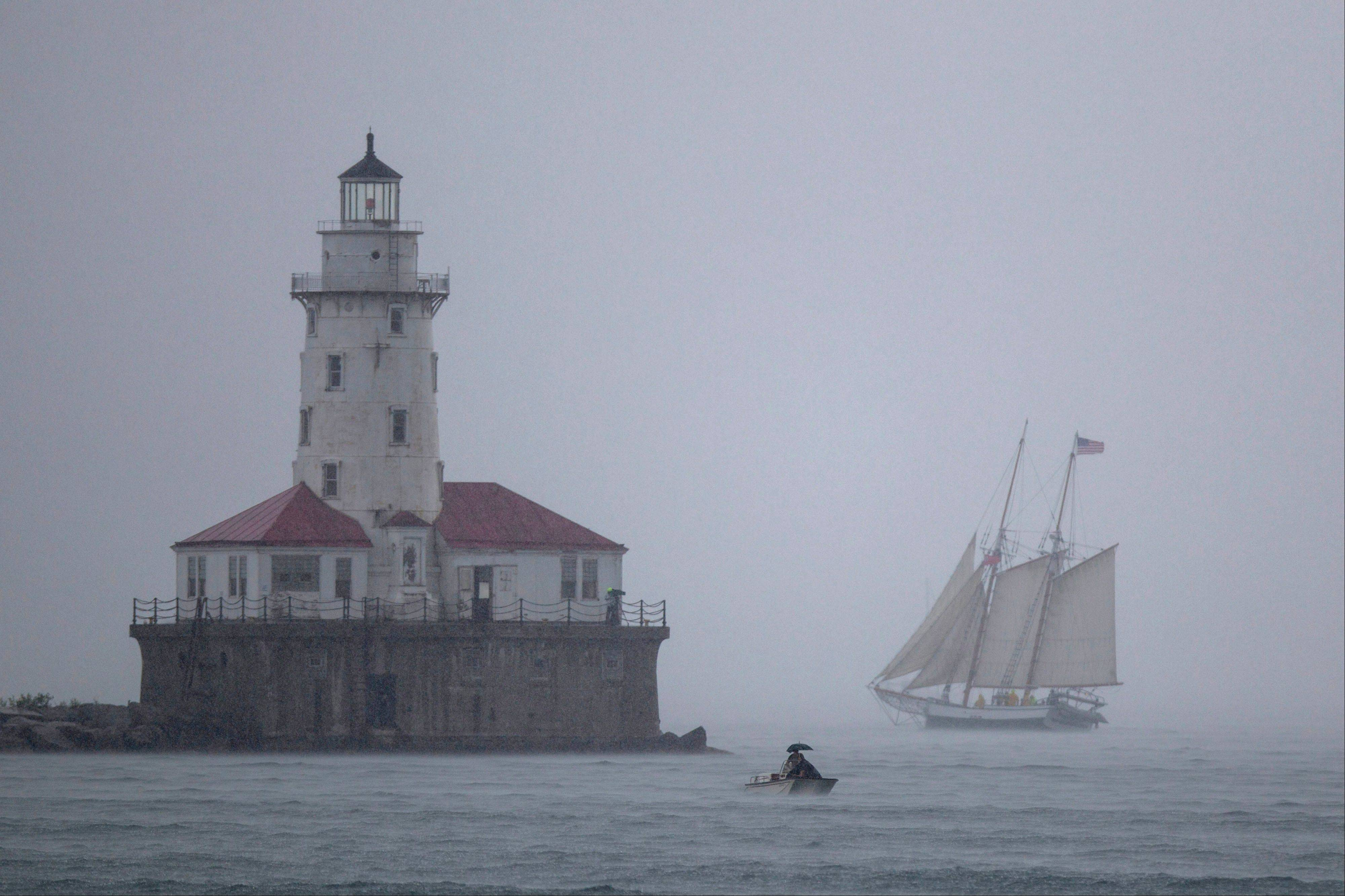 A sailing ship makes it past Chicago Harbor Light during a rainstorm Wednesday. A group of Tall Ships as well as racing sailboats are in Chicago through Sunday, Aug. 11