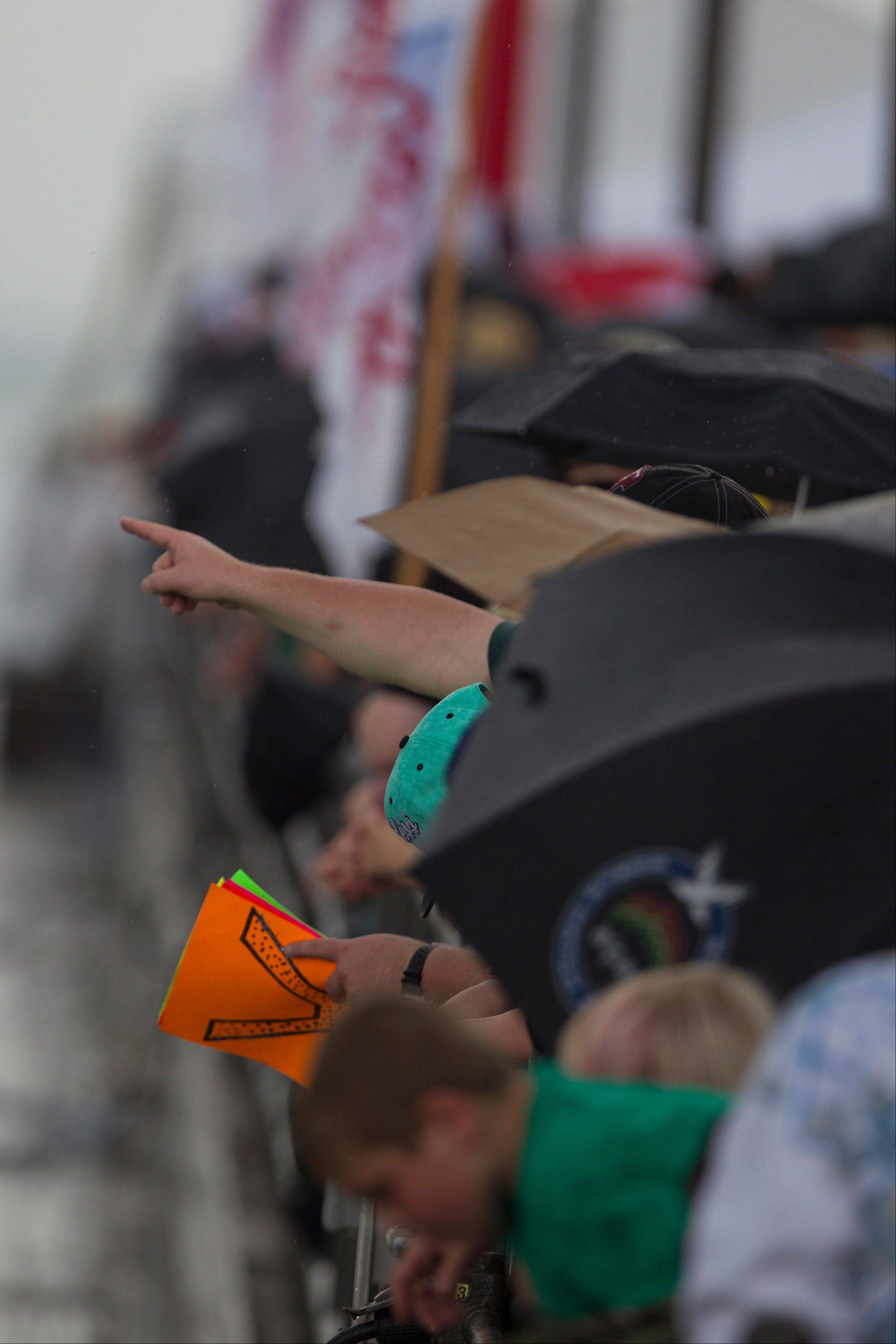 Spectators under umbrellas point at Tall Ships during a parade near Navy Pier in Chicago.