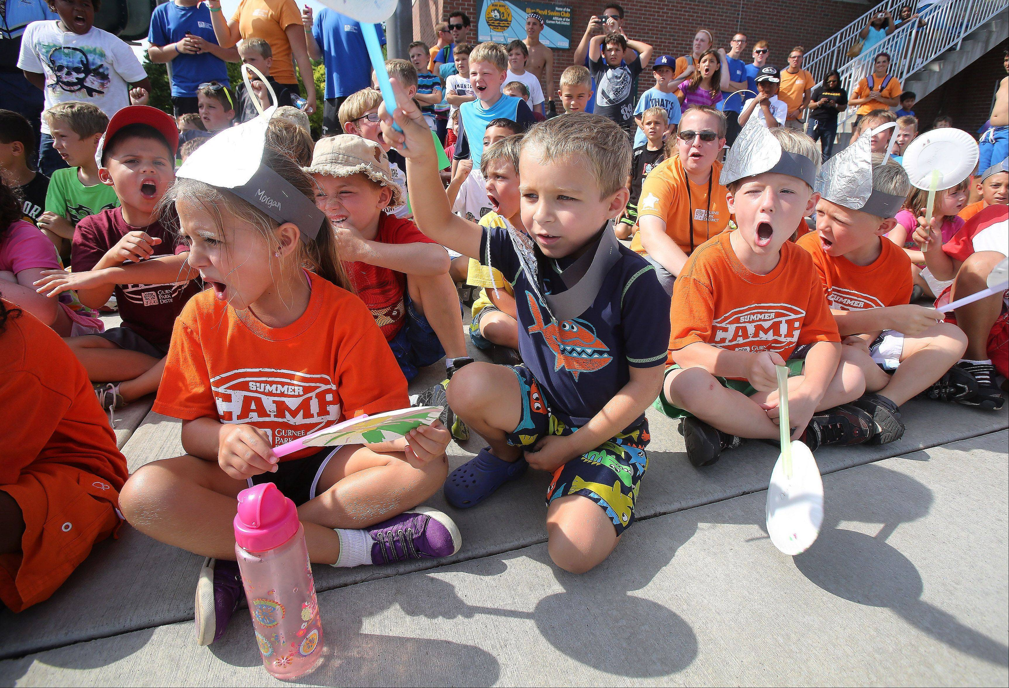 From left, 6-year-old Viking Discovery campers Morgan Ghys, Lucas Jablonski and Dean Foster yell encouragement to their favorites boats.